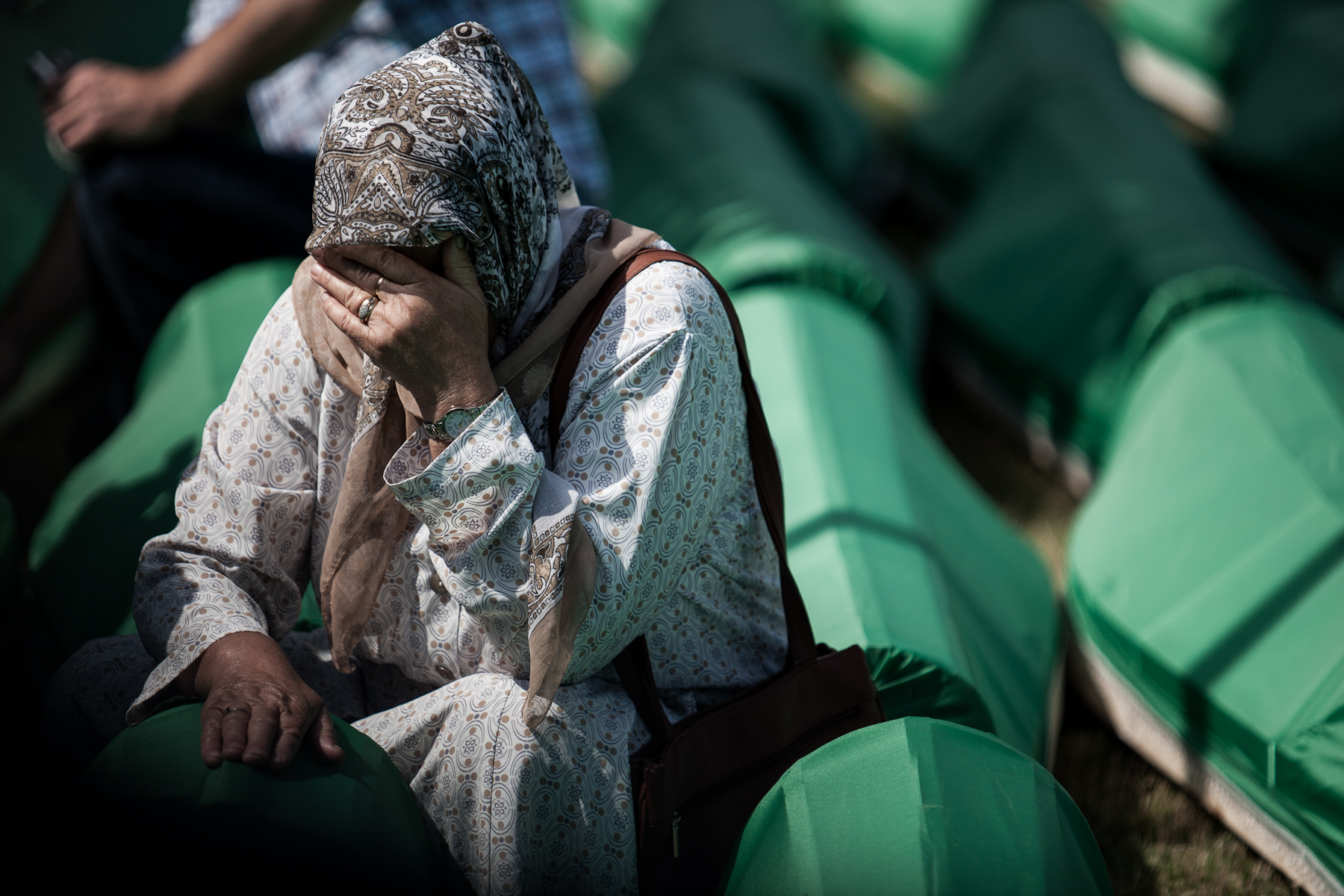 A woman cries at the coffin of a loved one at the Potocari cemetery in Srebrenica on July 11, 2010, before the memorial ceremony and mass burial of 775 newly identified victims of the 1995 Srebrenica massacre.