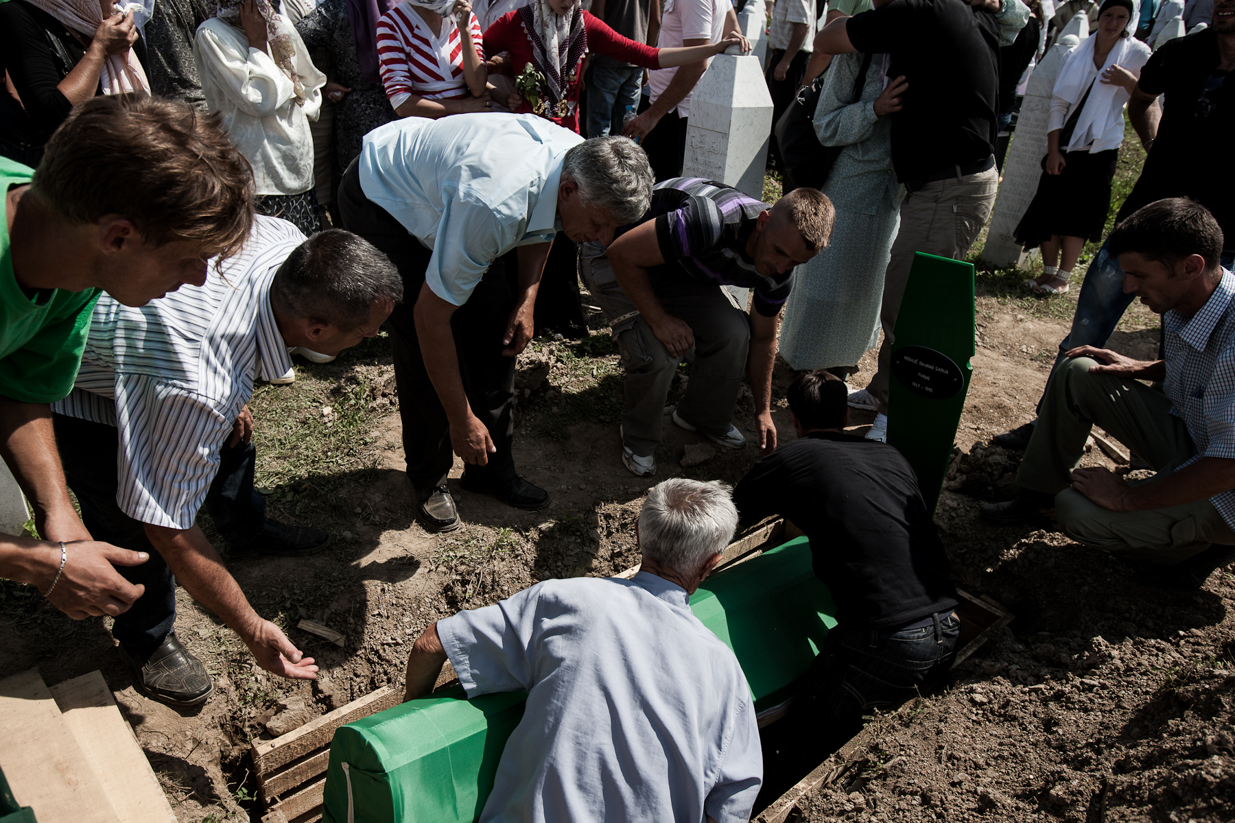 A coffin is layed into a grave at the Potocari cemetery during the mass burial of 775 newly identified victims of the 1995 Srebrenica massacre in Potočari cemetery, July 11, 2010.