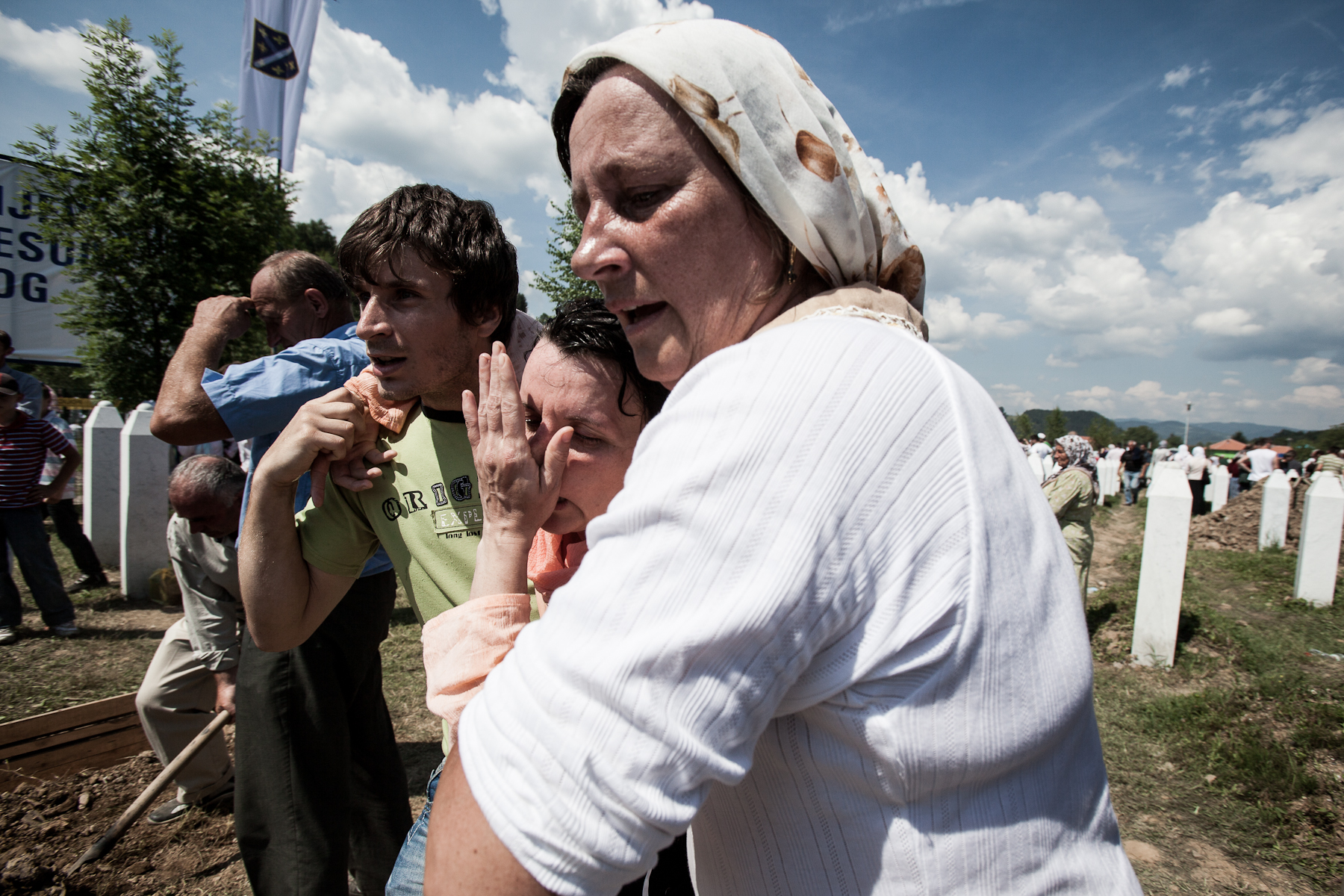 A woman who fainted is taken to the ambulance during the mass burial of 775 newly identified victims of the 1995 Srebrenica massacre in Potocari cemetery, July 11, 2010.