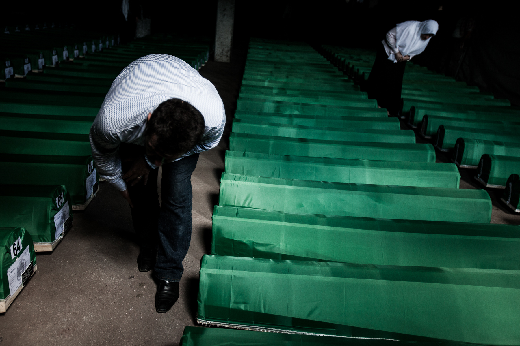 A man and a woman search for their relatives remains among rows of coffins that would be buried the next day at the Potocari memorial center.