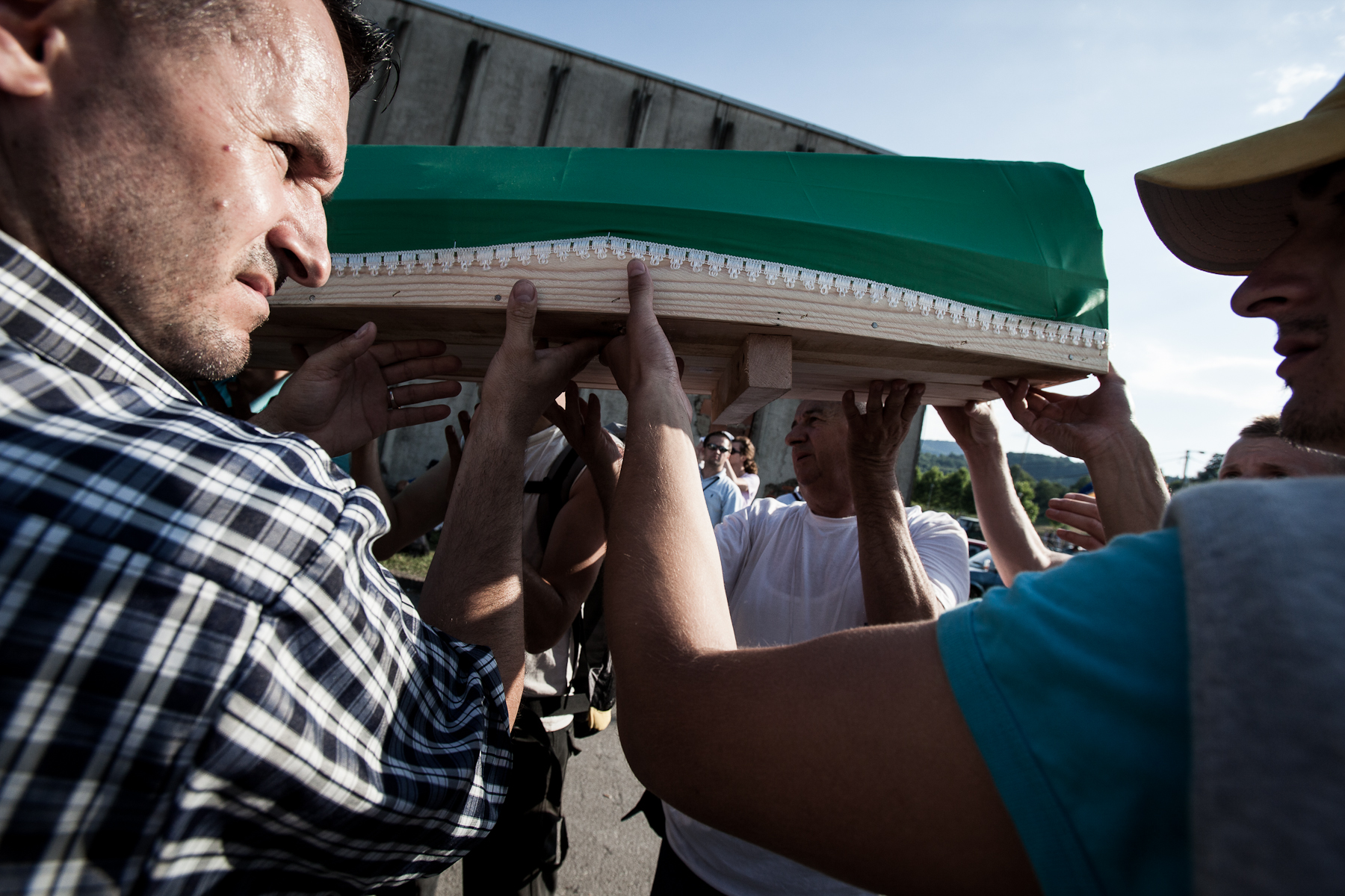 Coffins are carried from the hall to the Potocari cemetery where they will wait to be buried the next day.