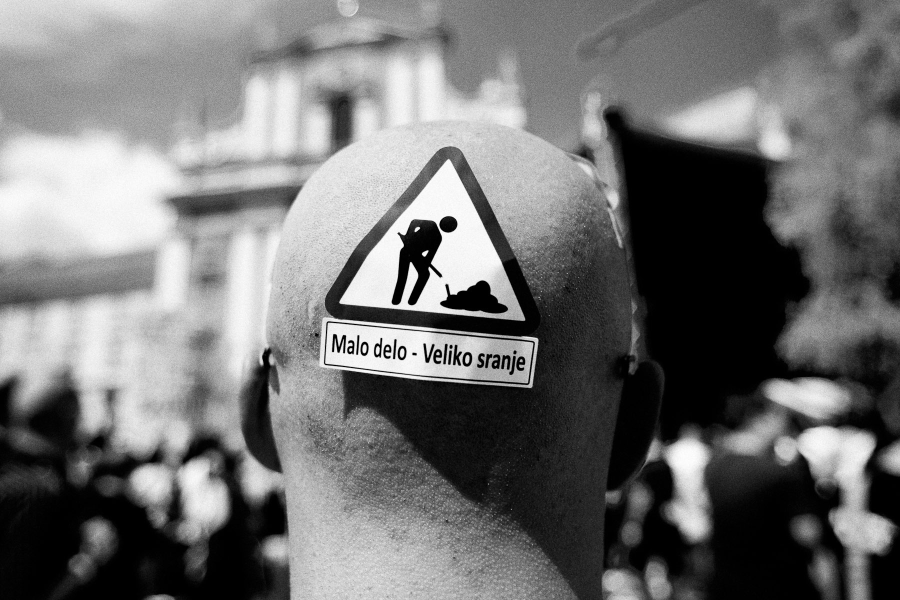 A protester wears an anti-government sticker on his head during a protest in Prešeren Square in Ljubljana, May 19, 2010. The sticker reads: Small labour - big shit.
