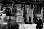 Riot police stand in front of a damaged entrance to the parliament building during anti-government student protests in Ljubljana, May 19, 2010.