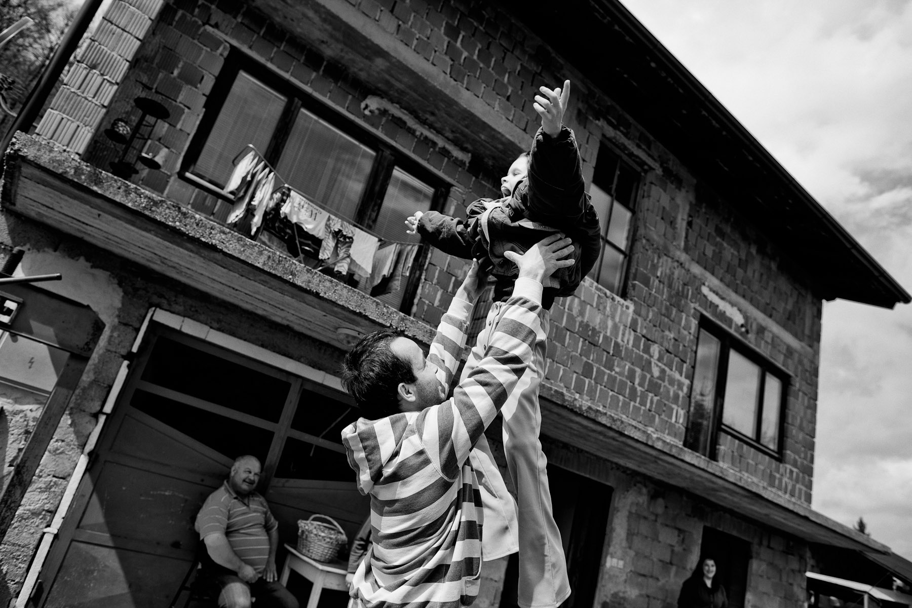 Barbara's brother Andrej throws Barbara in the air in a play Barbara loves a lot, in front of their house in Zavrc, Slovenia, April 7, 2012.