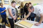 Trušnovec shows how to prepare the basis for a honeycomb to students and teachers during a beekeeping class at the Ljubljana Secondary School of Trade. Among other activities, beekeeping school classes are a project started by the Slovenian Beekeepers Association and supported by the government. They are highly succesful.