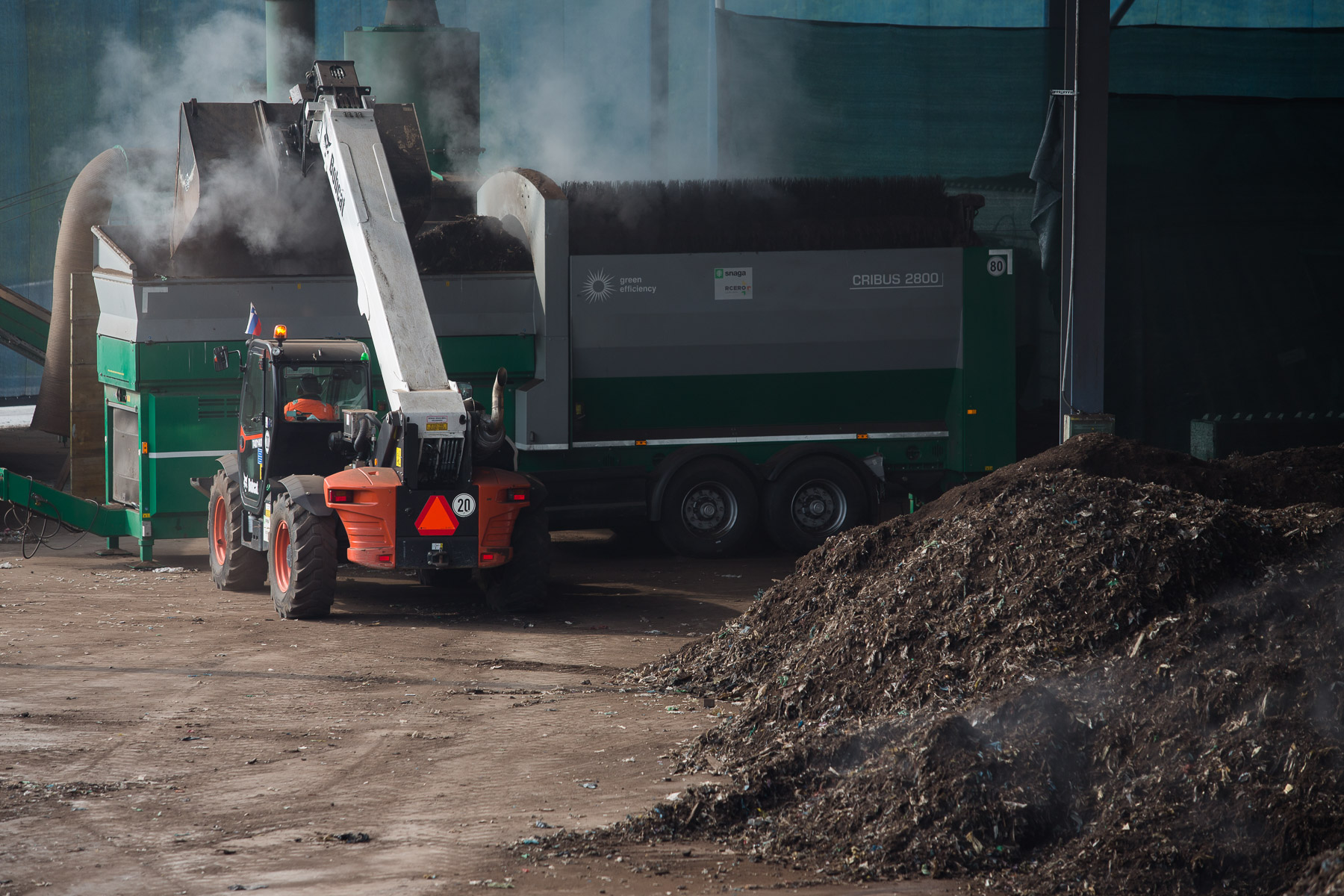 A loader dumps biomass into a sieving machine in the composting facility of RCERO Ljubljana.