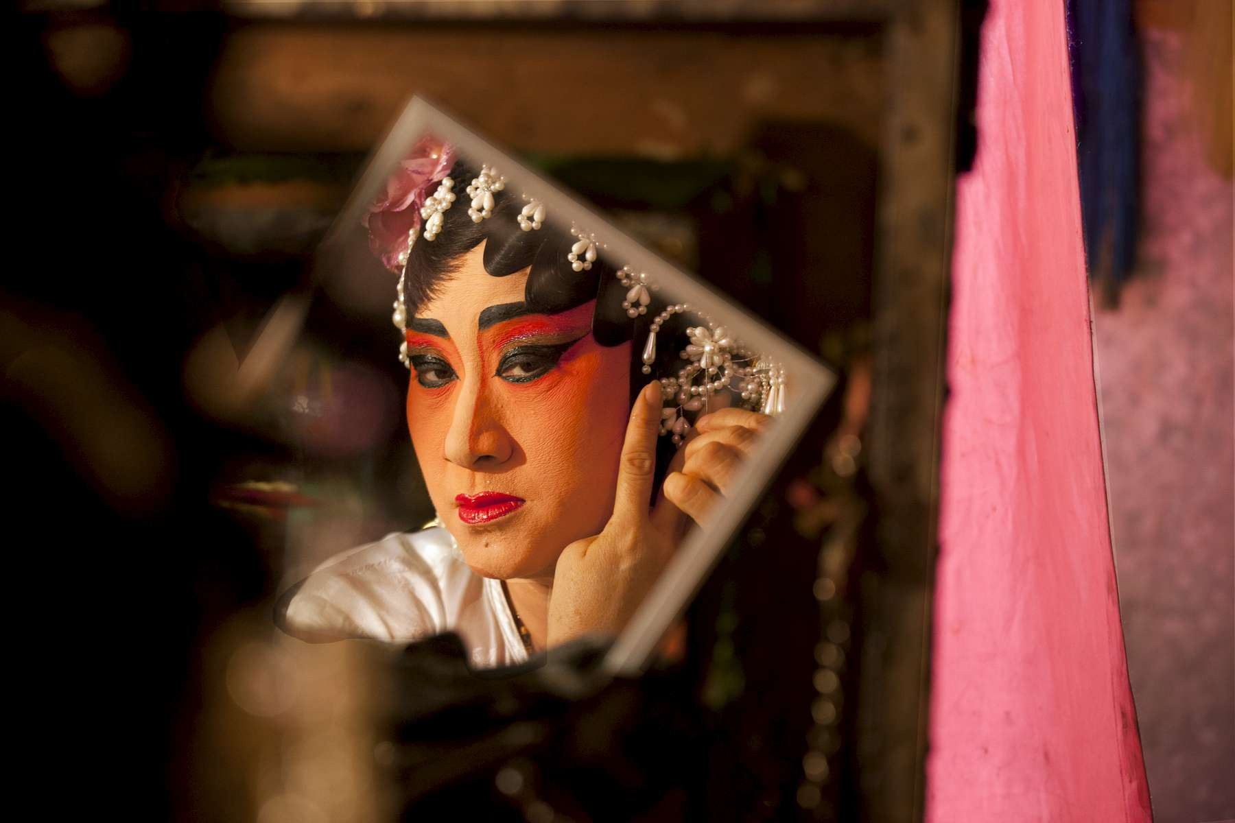 BANGKOK, THAILAND - JANUARY 25:  Jeng gets ready backstage she is with the Lao Yi Lai Heng Chinese opera  troupe as they act out the Teochew (Chaozhou) opera at the Plub Plachai temple on January 25, 2012 in Bangkok, Thailand. The traditional Chinese art form involving music, singing, martial arts and acting has a history of more than 500 years. There are about 30 members working with the group doing specials shows all week to celebrate the Chinese New year. The Chinese opera is popular in many parts of China,  Malaysia, Singapore, Thailand and Macau .(Photo by Paula Bronstein/Getty Images)