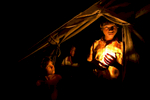 SITTWE, MYANMAR - NOVEMBER 23:  A Rohingya holds a candle outside his tent at a crowded IDP camp November 23, 2012 on the outskirts of Sittwe, Myanmar. An estimated 111,000 people were displaced by sectarian violence in June and October effecting mostly the ethnic Rohingya people who are now living in crowded IDP camps racially segregated from the Rakhine Buddhists in order to maintain stability. Around 89 lives were lost during a week of violence in October, the worst in decades. As of 2012, 800,000 Rohingya live in Myanmar. According to the UN, they are one of the most persecuted minorities in the world. (Photo by Paula Bronstein/Getty Images)