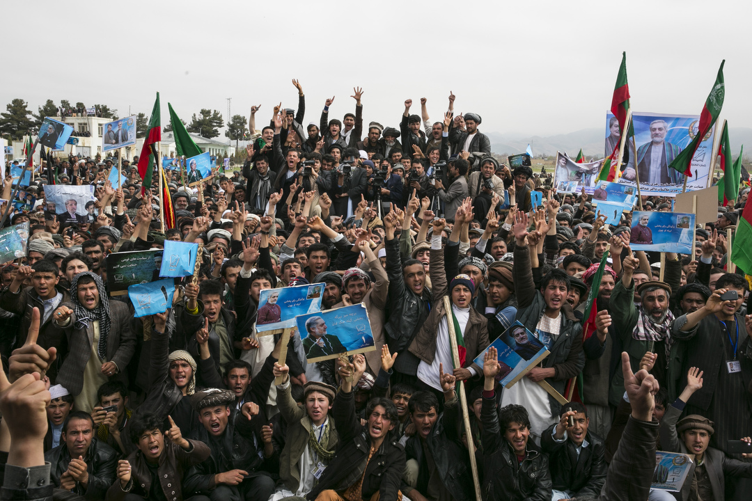 MAYMANA, AFGHANISTAN -APRIL 2: Afghan male supporters cheer as they attend a campaign rally for presidential candidate Abdullah Abdullah in Maymana, Faryab province, Afghanistan on April 2, 2014. In Kabul today a suicide bomber wearing a military uniform killed six police officers inside the Interior Ministry compound. This is the latest violence as the Taliban continues to try and disrupt this weekend's presidential election. The election is the third presidential poll since the fall of the Taliban. (Photo by Paula Bronstein/ for the Wall Street Journal)
