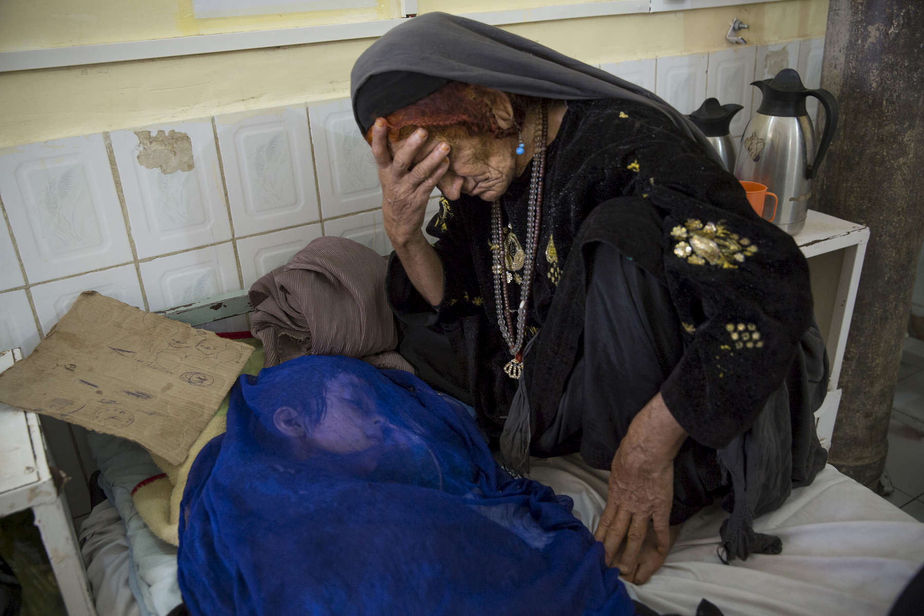 Sangina, mourns as she is told her grand daughter won\'t survive.  Critical ill  Fauzia is 8 years, in a coma with Meningitis and Tuberculosis  in the Pediatric Intensive Care Unit  at Boost hospital in Lashkah Gar, Afghanistan. Fauzia\'s mother died six months prior from complications due to child birth. June 22, 2014