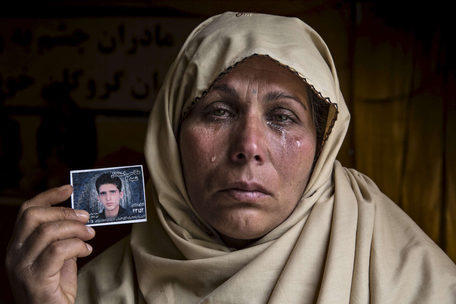 KABUL, AFGHANISTAN - April 18, 2015: Bibi Aisha cries holding a photo of her son, Yousef, 22, who was kidnapped and after many weeks with no answer she worries he will be killed.The Hazara community is asking for the Afghan government to help in finding the abducted Hazara. In late February gunmen seized 31 Hazara in Zabul  province in southern Afghanistan. The men were traveling from Iran by bus when they were attacked.April 18, 2015(Photo by Paula Bronstein/ for the Wall Street Journal)
