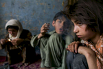Zaher, 14, smokes heroin along side his heroin addicted mother Sabera and her 11 year-old sister, Gulparai, at their home in Kabul.  The children began smoking after watching their widowed mother, a heroin addict for 4 years. August 27, 2007