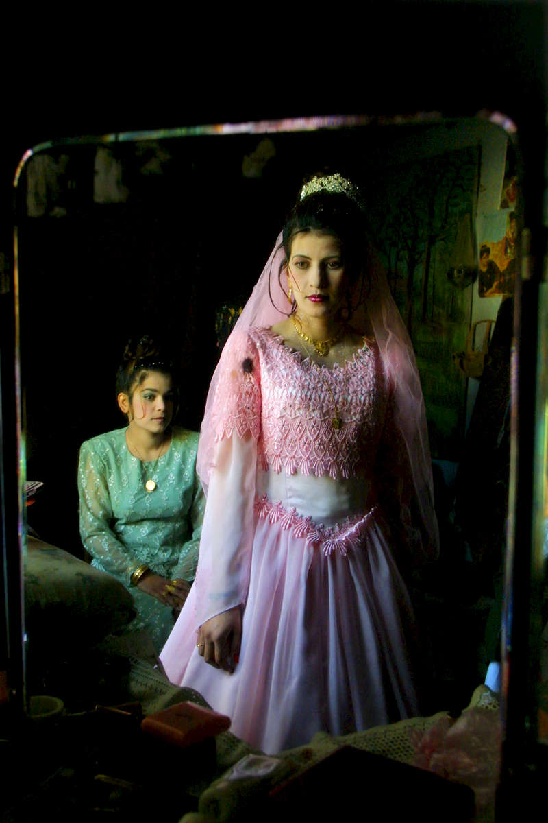 Najila Ahmadi the bride to be gets her wedding dress ready at the local beauty parlor where family help get her dressed for the big engagement party in Kabul. January 4, 2001