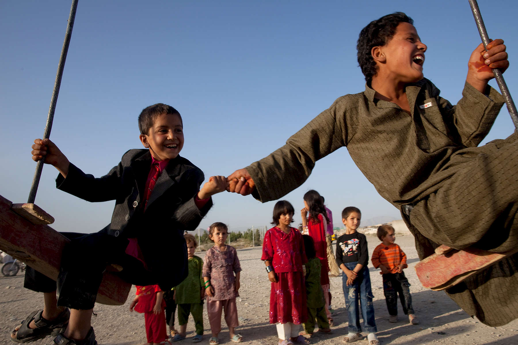KABUL, AFGHANISTAN - SEPTEMBER 20: Afghan boys hold hands as they swing on a merry-go-round celebrating the first day of Eid-al-Fitr, a three day holiday marking the end of the fasting month of Ramadan September 20, 2009 in Kabul, Afghanistan. During the holiday Afghans visit friends and family exchanging gifts and feasting. (Photo by Paula Bronstein/Getty Images)