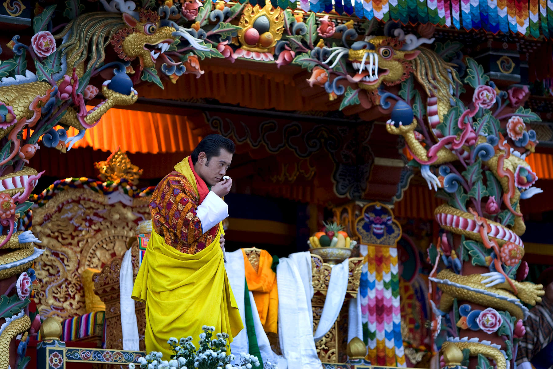 THIMPHU, BHUTAN -NOV 6, 2008: His Majesty Jigme Khesar Namgyel Wangchuck, 28, smells the flowers at the ceremonial grounds of The  Tendrey Thang November 6, 2008 in Thimphu, Bhutan. The young Bhutanese king, anOxford-educated bachelor became the youngest reigning monarch on the planet today. He was handed the Raven Crown by his father, the former King Jigme Singye Wangchuck, in an ornate ceremony in Thimpu, the capital. The tiny Himalayan kingdom, a Buddhist nation of 635,000 people is wedged between China and India .  (Photo by Paula Bronstein/Getty Images)