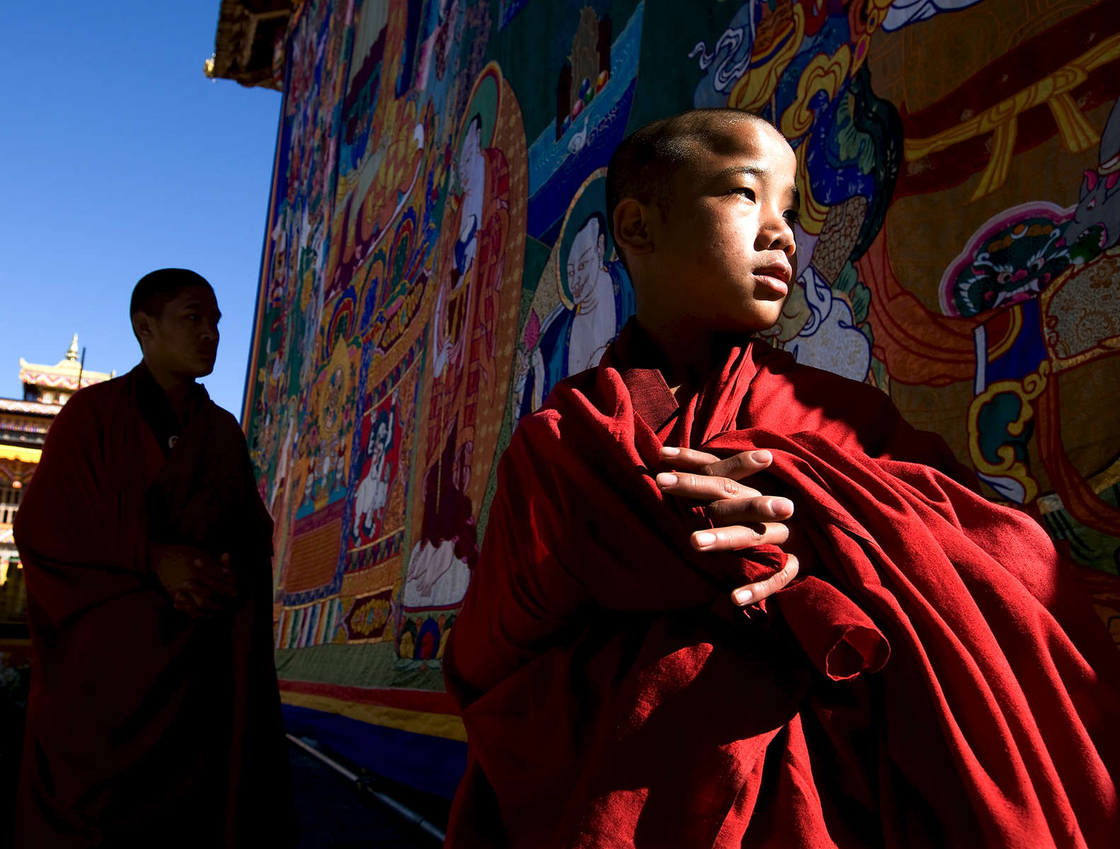 THIMPHU, BHUTAN -NOV 6, 2008: Bhutanese monks stand next to a large Thangkha painting at the Dratshang Kuenra Tashichho Dzong waiting for His Majesty Jigme Khesar Namgyel Wangchuck to arrive for the Coronation ceremony November 6, 2008 in Thimphu, Bhutan. The young Bhutanese king, anOxford-educated bachelor became the youngest reigning monarch on the planet today. He was handed the Raven Crown by his father, the former King Jigme Singye Wangchuck, in an ornate ceremony in Thimpu, the capital. The tiny Himalayan kingdom, a Buddhist nation of 635,000 people is wedged between China and India .  (Photo by Paula Bronstein/Getty Images)