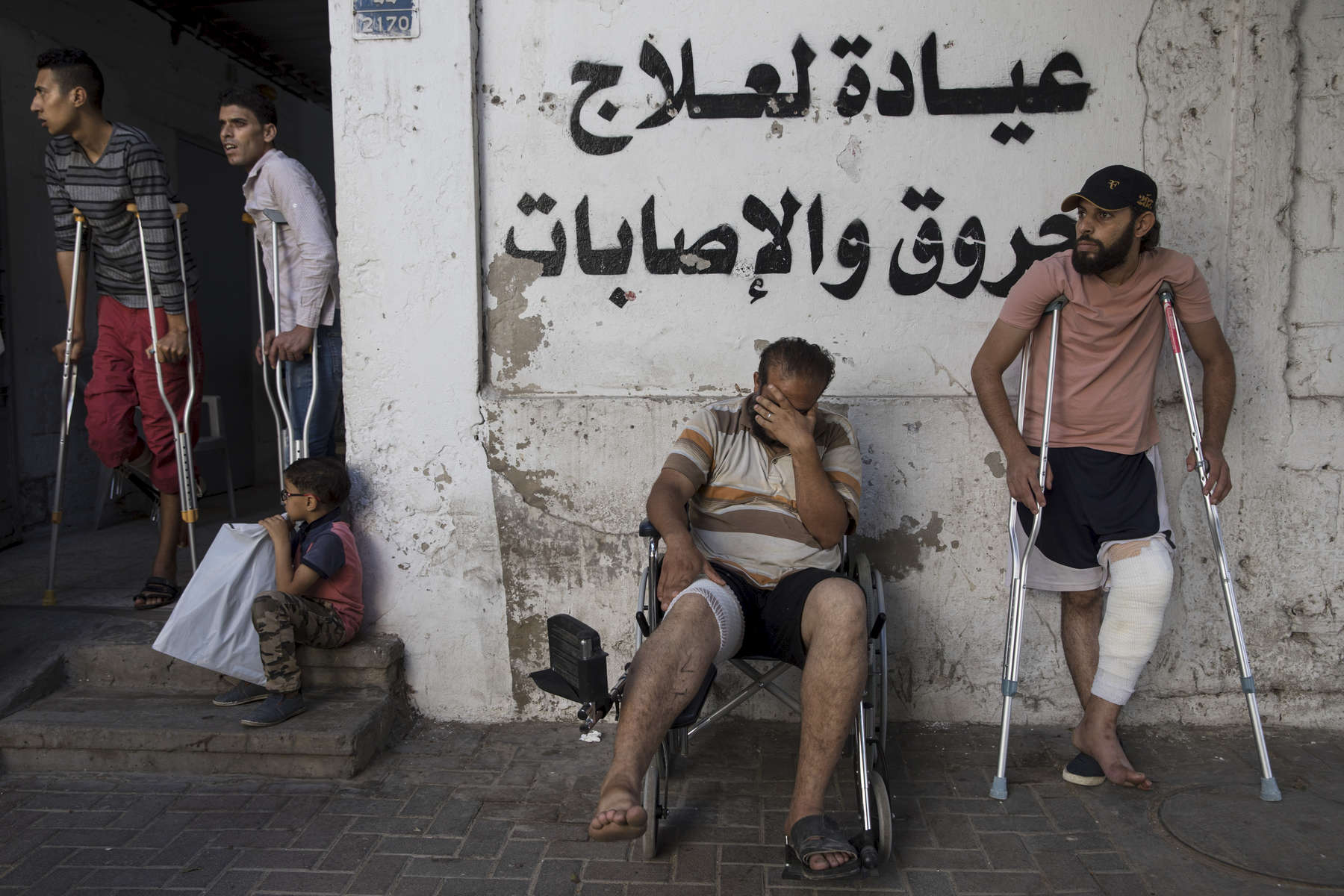 GAZA CITY, GAZA STRIP- MAY 17,2018: At the Médecins Sans Frontières (MSF) clinic male patients are lined up awaiting medical treatment on May 17,2018 in Gaza city, Gaza strip. MSF has focused their attention on treating injuries  caused by bullet wounds. According to the International Committee of the Red Cross (ICRC), 13,000 Palestinians were wounded (as of June 19, 2018), the majority severely, with some 1,400 struck by three to five bullets. No Israelis were physically harmed during this time period, Israel's use of deadly force was condemned during the UN general assembly on June 13 th along with other human rights organizations. The Israeli military (IDF) started using new weaponry, explosive bullets that shatter bones, tissue, destroying veins and arteries, the aim is to create a handicapped community, especially amongst the young male population. Many of the wounded protesters have to undergo multiple surgeries to try to save their limbs, and in some cases amputation is the only solution. With limited healthcare available in Gaza many were sent to Jordan and Turkey for further treatment. More issues that plague Gaza include a water supply that is 95 percent contaminated and a population forced to live without electricity for 21 hours a day. Gaza is compared to Venezuela with almost half of it's labor force unemployed. Everyone is well aware that Gaza's two million inhabitants are trapped in a cycle of violence and poverty, living in an open air prison. The problems and complications affecting Gaza today are overwhelming. The world, seemingly accustomed to the suffering of the Gazan people turns a blind eye. (Photo by Paula Bronstein )