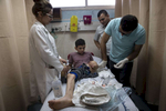 GAZA CITY, GAZA STRIP- MAY 29,2018 Abdullah Al-Anqar, 13, gets medical treatment for his amputated leg at the Al-Shifa hospital on May 29,2018 in Gaza city, Gaza strip. He was shot by twice in his leg at close range with explosive bullets, one in his upper thigh and the other under his knee on May 3rd. He was climbing the Israeli border fence when he was severely injured. The Israel soldiers decided to see his life, dragging him through the border fence, then he was flown to Soroka hospital in Beer Shaba, Israel where he spent 16 days in Intensive care, his leg was amputated there as well. The Israeli military (IDF) started using new weaponry, explosive bullets that shatter bones, tissue, destroying veins and arteries, the aim is to create a handicapped community, especially amongst the young male population. Many of the wounded protesters have to undergo multiple surgeries to try to save their limbs, and in some cases amputation is the only solution. Everyone is well aware that Gaza's two million inhabitants are trapped in a cycle of violence and poverty, created by policies and political decisions on both sides. The problems and complications affecting Gaza today are overwhelming. The world, seemingly accustomed to the suffering of the Gazan people turns a blind eye. (Photo by Paula Bronstein )