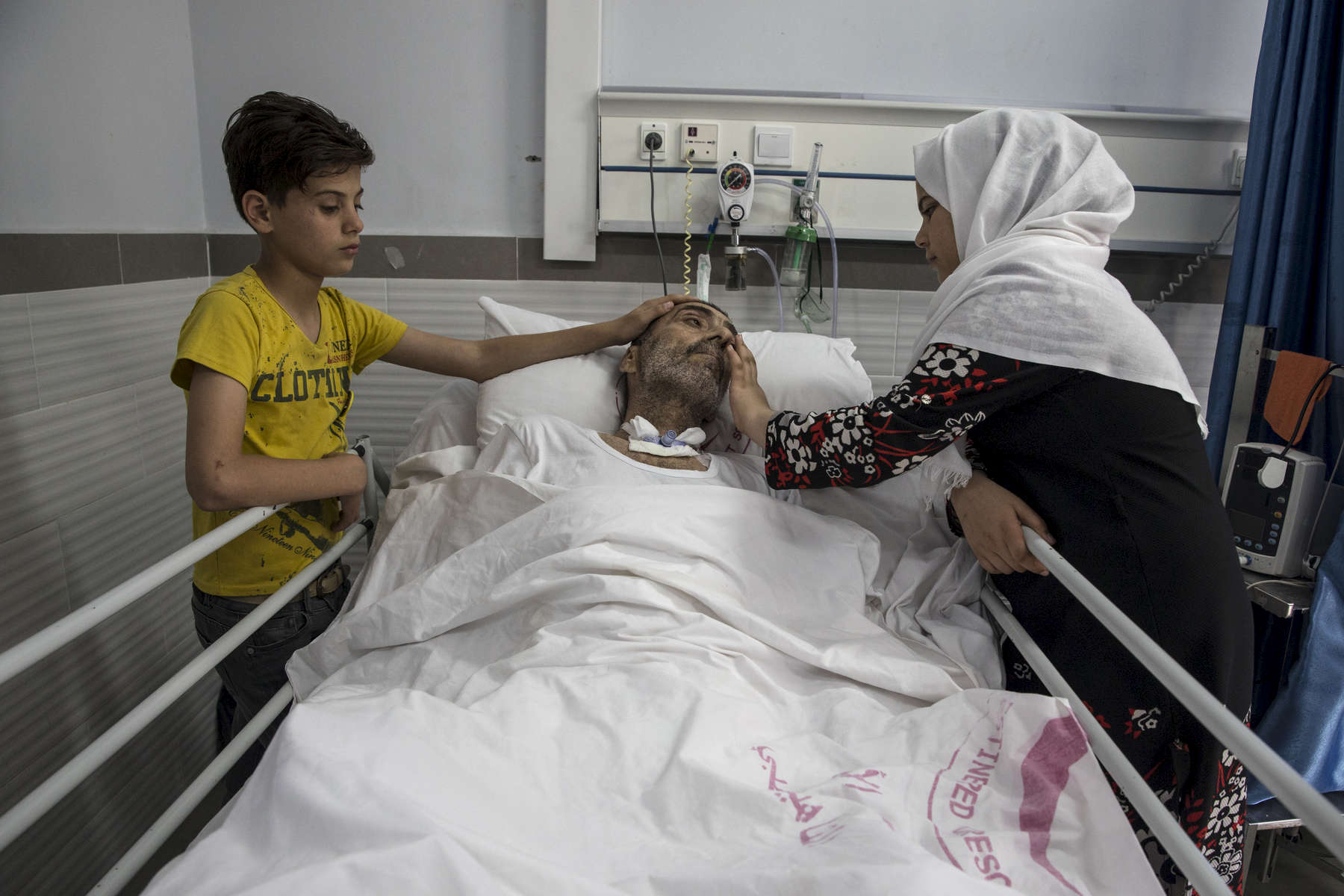 GAZA STRIP- MAY 19,2018 : Rashad Al-Baba, 58, shot twice by Israeli forces is cared for by his grand children at the Red Crescent Rehabilitation Center of Al-Amal on May 19,2018 in Gaza strip. He was injured on March 30th when he arrived to the protest near Rafah looking to protect his grand children who went there without his knowledge. After the injury, Rashad suffered a heart attack, spending 27 days in the intensive care unit. The problems and complications affecting Gaza today are overwhelming. The world, seemingly accustomed to the suffering of the Gazan people turns a blind eye. (Photo by Paula Bronstein )