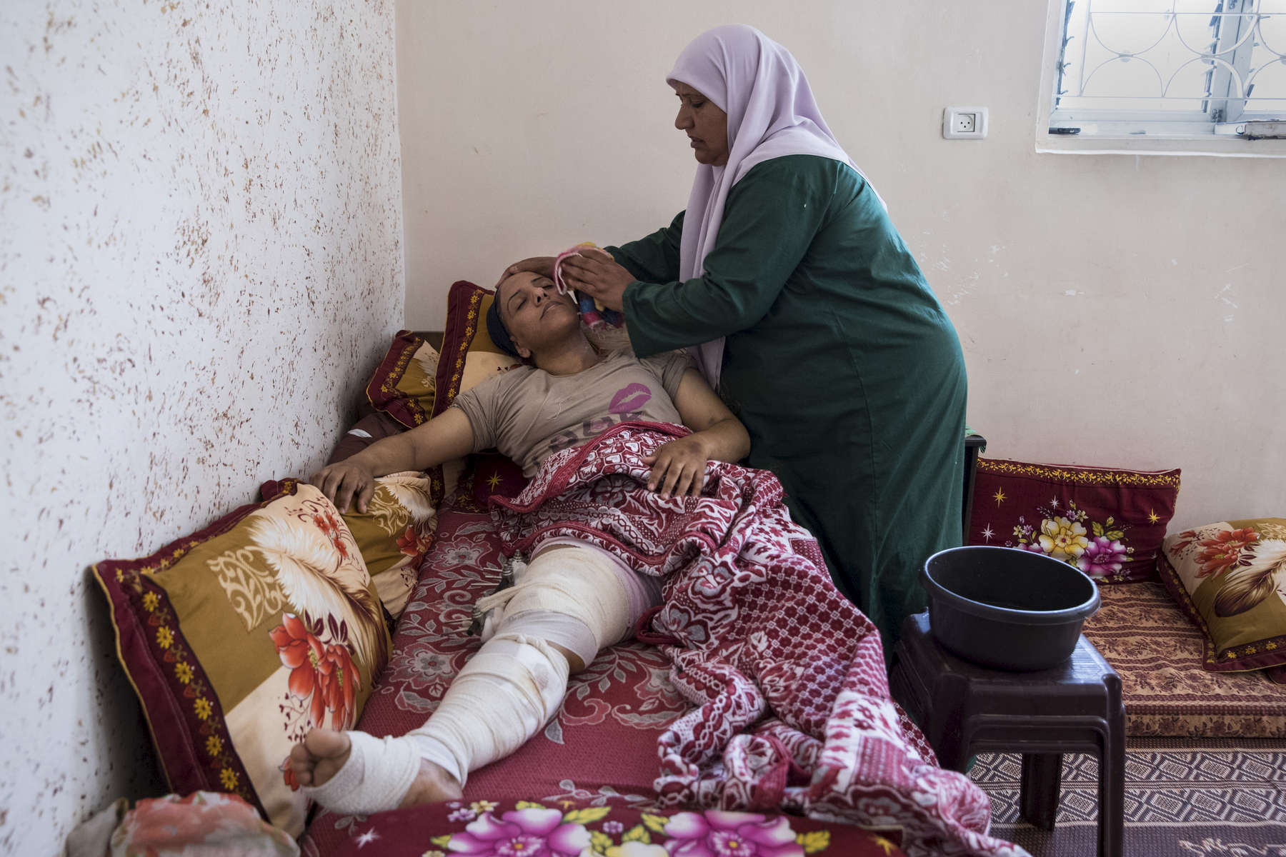 GAZA CITY, GAZA STRIP- MAY 25,2018 : Dawlat Fawzi Hamadin, 33, from Beit Hanoun, gets washed by her mother on May 25, 2018 in Gaza. She was shot on May 14th,  damaging the main artery of the heart with severe tissue damage. Dawlat was pronounced dead, then after an operation that lasted for seven hours she survived. She is the only breadwinner of the family and worked as a hairdresser. Everyone is well aware that Gaza's two million inhabitants are trapped in a cycle of violence and poverty, created by policies and political decisions on both sides. The problems and complications affecting Gaza today are overwhelming. The world, seemingly accustomed to the suffering of the Gazan people turns a blind eye. (Photo by Paula Bronstein )