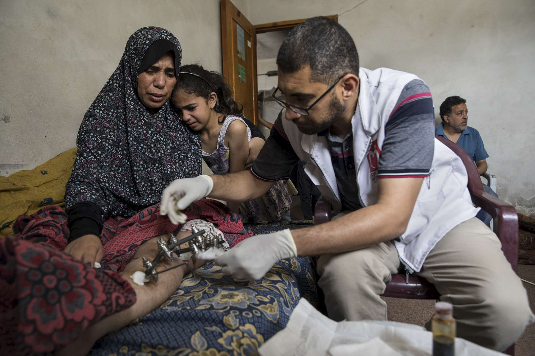 GAZA STRIP- MAY 22,2018 : Kefah Al-Ajrami, 47, holds her daughter Zamzam Al-Ajrami, 9 years while Dr. Naser Al-Sharif from the Turkish ngo Doctors Worldwide cleans and changes the bandages on her leg on May 22,2018 in Gaza city, Gaza strip. Kefah is a mother of seven, she was shot in her left leg with an exploding bullet causing extensive injury to her leg. She went to the protests on March 30th  along with her children and husband but was nowhere near fence.  The Israeli military (IDF) started using new weaponry, explosive bullets that shatter bones, tissue, destroying veins and arteries, the aim is to create a handicapped community, especially amongst the young male population.  Everyone is well aware that Gaza's two million inhabitants are trapped in a cycle of violence and poverty, created by policies and political decisions on both sides. The problems and complications affecting Gaza today are overwhelming. The world, seemingly accustomed to the suffering of the Gazan people turns a blind eye. (Photo by Paula Bronstein )
