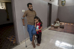 GAZA CITY, GAZA STRIP- MAY 22,2018 : Ahmad Abu Jaser, 31, father of four daughters, hugs his daughter Lyan, age 7, he sustained an injury in his leg along with his brother who was shot twice, in his thigh and back resting on the floor on May 22,2018 in Gaza city, Gaza strip.At least 110 Palestinians were killed during the between March 30-May 15th. According to the International Committee of the Red Cross (ICRC), 13,000 Palestinians were wounded (as of June 19, 2018), the majority severely, with some 1,400 struck by three to five bullets. No Israelis were physically harmed during this time period, Israel's use of deadly force was condemned during the UN general assembly on June 13 th along with other human rights organizations.Everyone is well aware that Gaza's two million inhabitants are trapped in a cycle of violence and poverty, created by policies and political decisions on both sides. The problems and complications affecting Gaza today are overwhelming. The world, seemingly accustomed to the suffering of the Gazan people turns a blind eye. (Photo by Paula Bronstein )