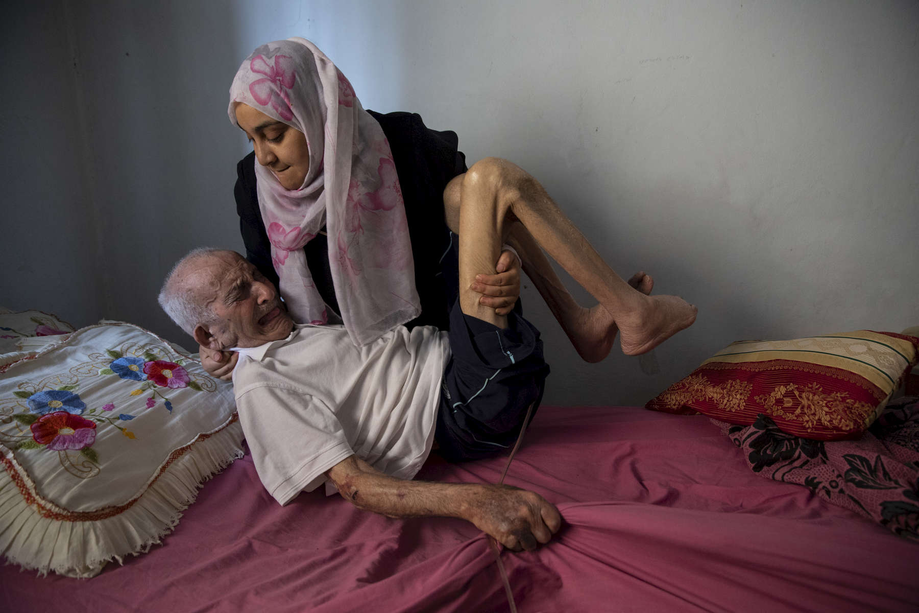 BEIT LAHIA, GAZA STRIP- MAY 28,2018Fadel Al-Zain, 70, is taken care of by his daughter Hana' Al-Zain on May 28,2018 in Beit Lahia, Gaza strip. He was injured in height of the 2014 offensive when bombing hit near his home. He is now paralyzed, quadriplegic, and can't function on his own after he suffered internal bleeding in his brain.The world's largest open air prison along the Israel-Gaza border. Everyone is well aware that Gaza's two million inhabitants are trapped in a cycle of violence and poverty, created by policies and political decisions on both sides. The problems and complications affecting Gaza today are overwhelming. The world, seemingly accustomed to the suffering of the Gazan people turns a blind eye. (Photo by Paula Bronstein )