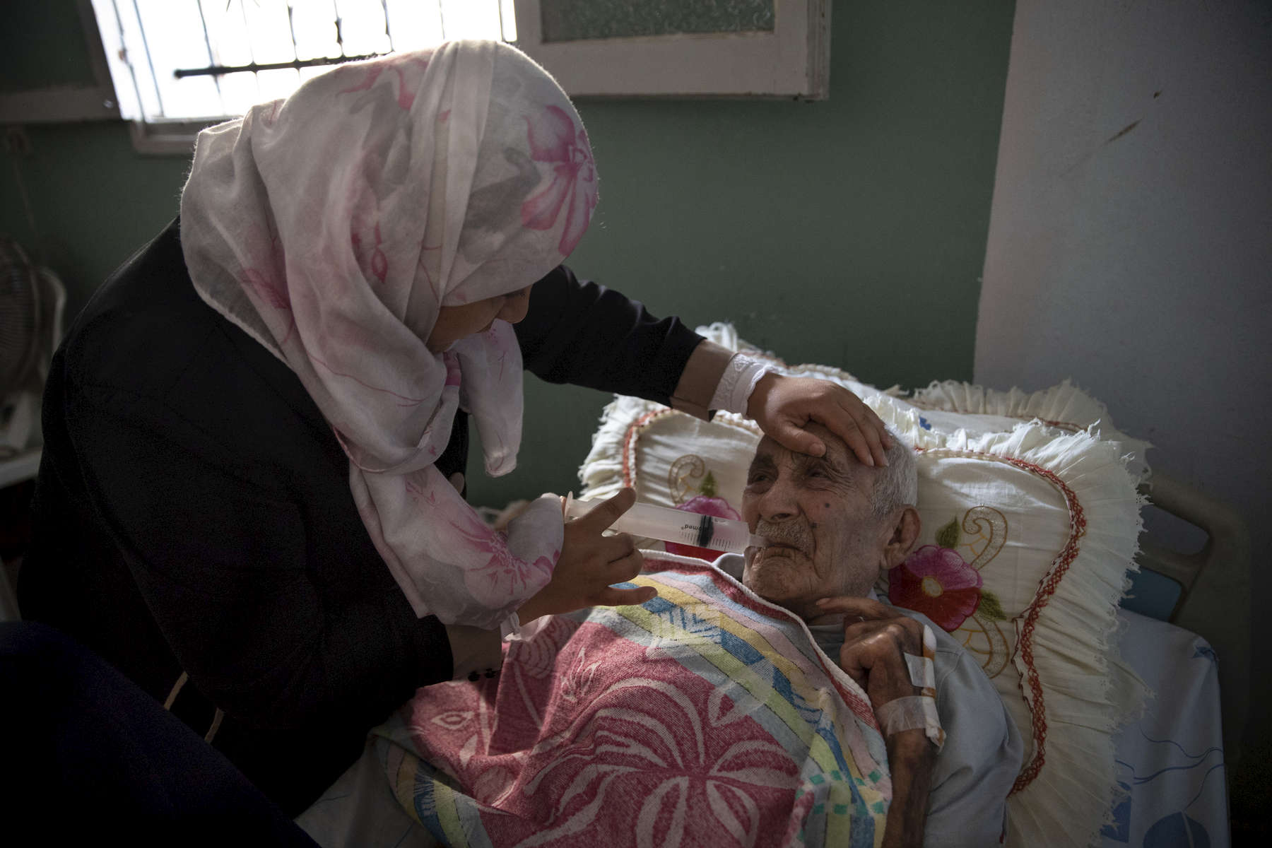 BEIT LAHIA, GAZA STRIP- MAY 27,2018Fadel Al-Zain, 70, is taken care of by his daughter Hana' Al-Zain on May 27,2018 in Beit Lahia, Gaza strip. He was injured in height of the 2014 offensive when bombing hit near his home. He is now paralyzed, quadriplegic, and can't function on his own after he suffered internal bleeding in his brain.The world's largest open air prison along the Israel-Gaza border. Everyone is well aware that Gaza's two million inhabitants are trapped in a cycle of violence and poverty, created by policies and political decisions on both sides. The problems and complications affecting Gaza today are overwhelming. The world, seemingly accustomed to the suffering of the Gazan people turns a blind eye. (Photo by Paula Bronstein )