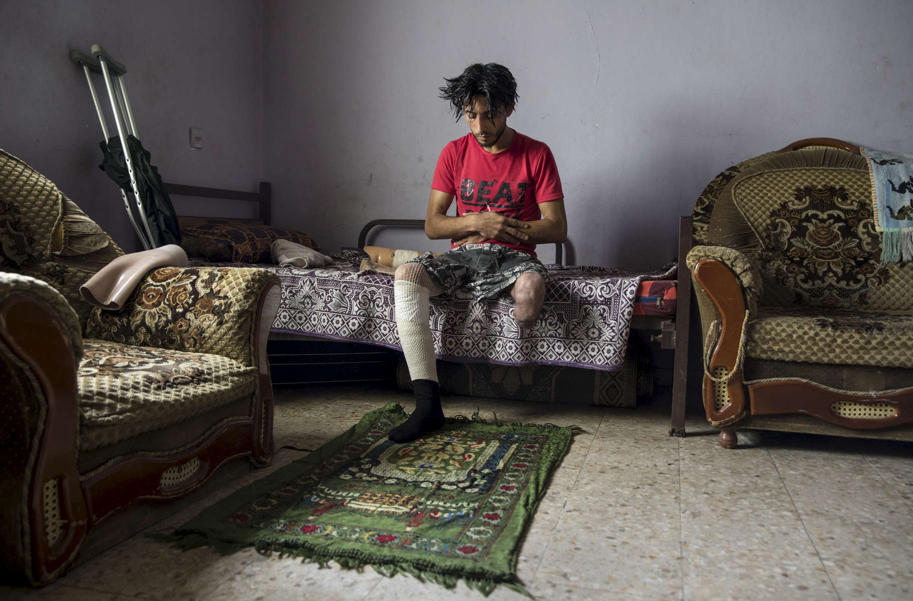 GAZA CITY, GAZA STRIP- MAY 23,2018: Iyad Manar Al-Dawhid, 28, prays in his home on May 23,2018 in Gaza city, Gaza strip. Iyad was injured again on April 7th at the protest when a bullet hit his prosthesis, injuring his other leg. He had his left leg amputated in a car accident in 2011. According to the International Committee of the Red Cross (ICRC), 13,000 Palestinians were wounded (as of June 19, 2018), the majority severely, with some 1,400 struck by three to five bullets. No Israelis were physically harmed during this time period, Israel's use of deadly force was condemned during the UN general assembly on June 13 th along with other human rights organizations.Everyone is well aware that Gaza's two million inhabitants are trapped in a cycle of violence and poverty, created by policies and political decisions on both sides. The problems and complications affecting Gaza today are overwhelming. The world, seemingly accustomed to the suffering of the Gazan people turns a blind eye. (Photo by Paula Bronstein )