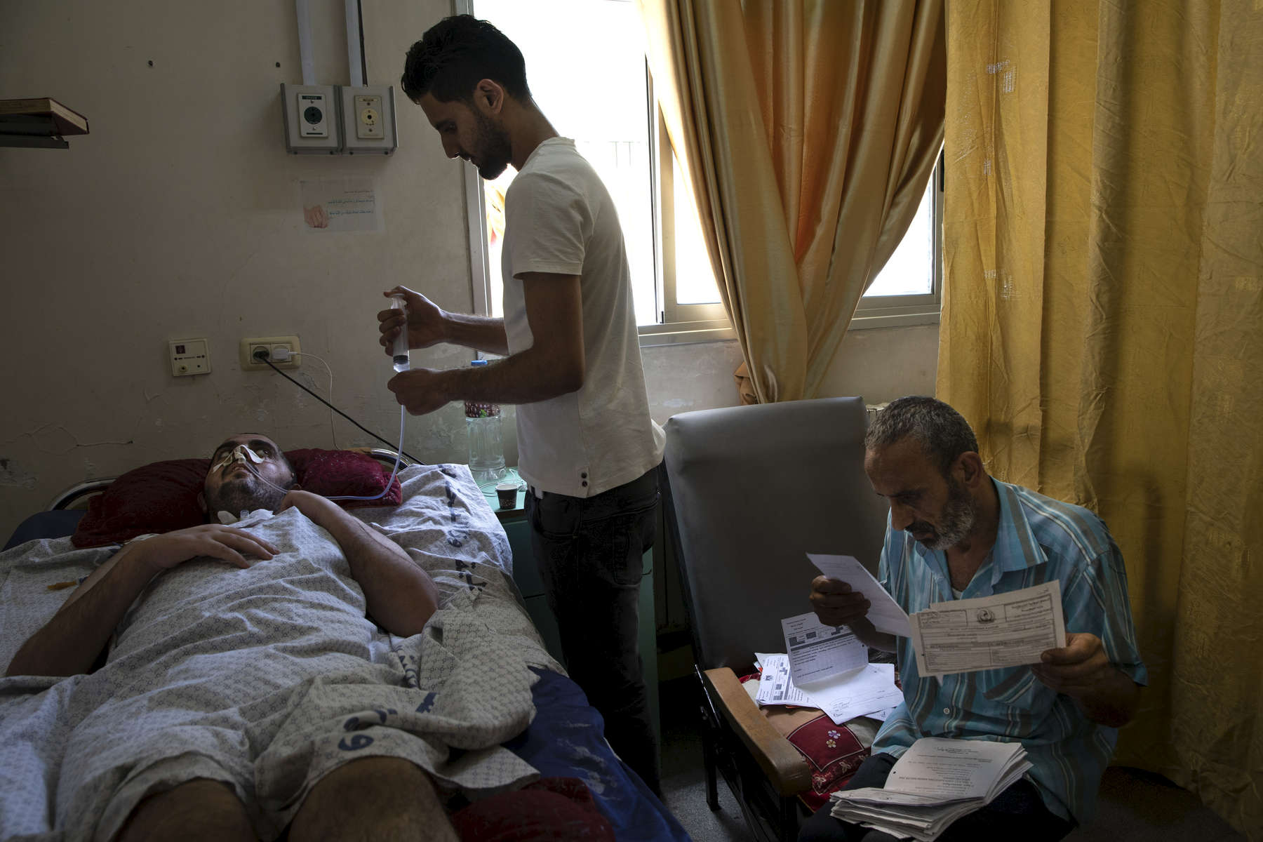 "GAZA CITY, GAZA STRIP- MAY 21,2018 Baraa' Hassan, 23,  suffers from a malignant brain tumor is seen at Rantisi hospital, one of the best medical facilities for Cancer,in Gaza city on May 21,2018. His case is serious, he was transferred to Hebron Hospital underwent a surgery to remove a part of the tumor. After the surgery he fell in a coma lasted for 45 days. His family still waits the Israeli permit under the pretext of ""security check"".   six months without response. His brother: Anas Hassan. on May 21,2018 in Gaza city, Gaza strip. He was shot by twice in his leg at close range with explosive bullets, one in his upper thigh and the other under his knee on May 3rd. He was climbing the Israeli border fence when he was severely injured. The Israel soldiers decided to see his life, dragging him through the border fence, then he was flown to Soroka hospital in Beer Shaba, Israel where he spent 16 days in Intensive care, his leg was amputated there as well. The Israeli military (IDF) started using new weaponry, explosive bullets that shatter bones, tissue, destroying veins and arteries, the aim is to create a handicapped community, especially amongst the young male population. Many of the wounded protesters have to undergo multiple surgeries to try to save their limbs, and in some cases amputation is the only solution. Everyone is well aware that Gaza's two million inhabitants are trapped in a cycle of violence and poverty, created by policies and political decisions on both sides. The problems and complications affecting Gaza today are overwhelming. The world, seemingly accustomed to the suffering of the Gazan people turns a blind eye. (Photo by Paula Bronstein )"