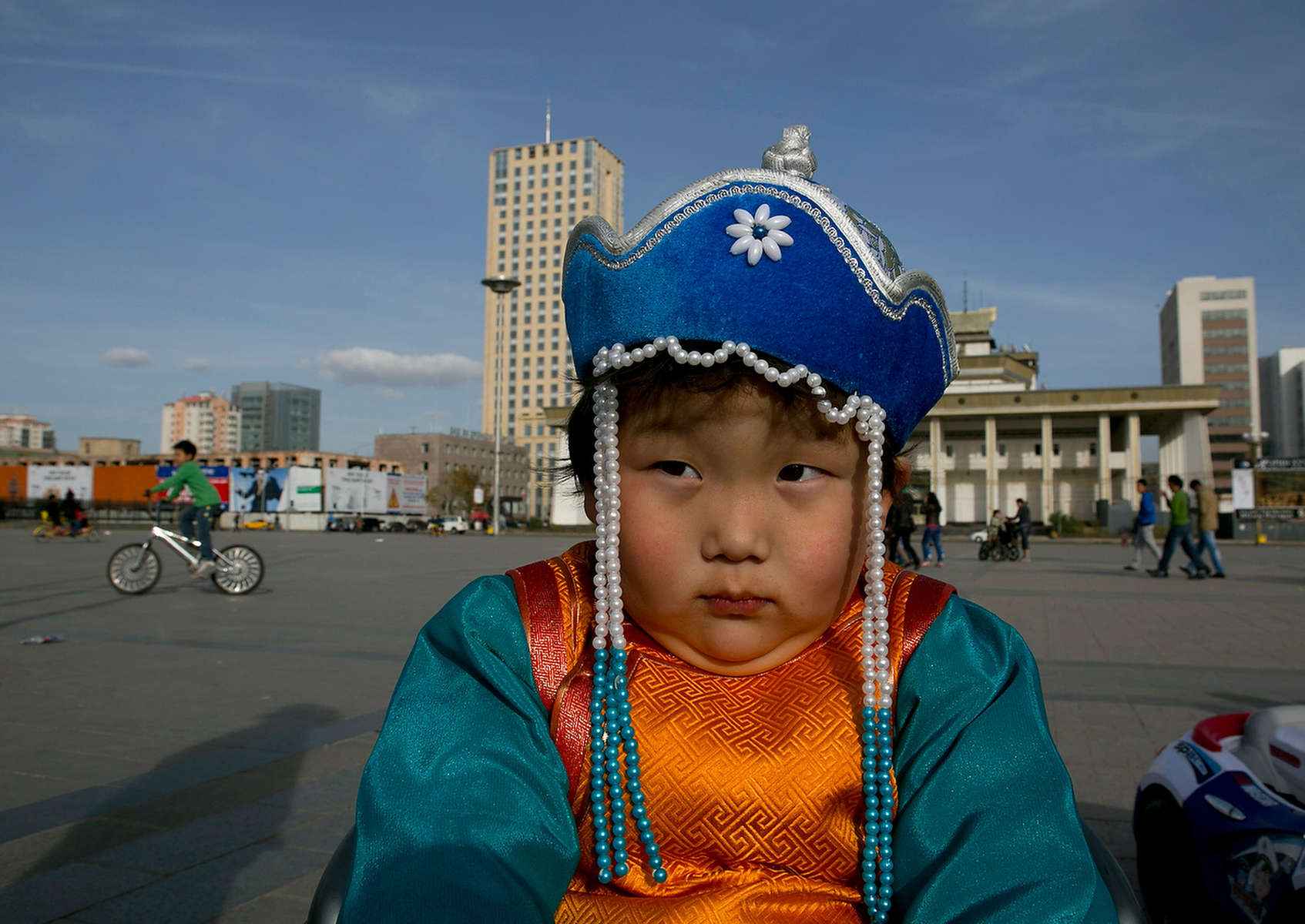 ULAANBATAAR, MONGOLIA - OCTOBER 18: A young Mongolian boy sits in a motorized toy car wearing traditional dress at Sukhbataar Square October 18, 2012 Ulaanbataar, Mongolia. Some 100 years ago, Mongolia gained independence from Qing China, and more than 20 years ago it removed itself from the Soviet Bloc. Since then, the country has been undergoing massive social, economic and political changes. The Oyu Tolgoi, the copper and gold mine is Mongolia's biggest foreign investment project to date adding an estimated 35% value to the country's GDP. Mongolia is a land of amazing contrasts and is the most sparsely populated country on earth with fewer than 3 million people. (Photo by Paula Bronstein/Getty Images)