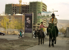 ULAANBATAAR, MONGOLIA - OCTOBER 18: Mongolians  herders walk their horses past a building under construction October 18, 2012 Ulaanbataar, Mongolia. Some 100 years ago, Mongolia gained independence from Qing China, and more than 20 years ago it removed itself from the Soviet Bloc. Since then, the country has been undergoing massive social, economic and political changes. The Oyu Tolgoi, the copper and gold mine is Mongolia's biggest foreign investment project to date adding an estimated 35% value to the country's GDP. Mongolia is a land of amazing contrasts and is the most sparsely populated country on earth with fewer than 3 million people. (Photo by Paula Bronstein/Getty Images)