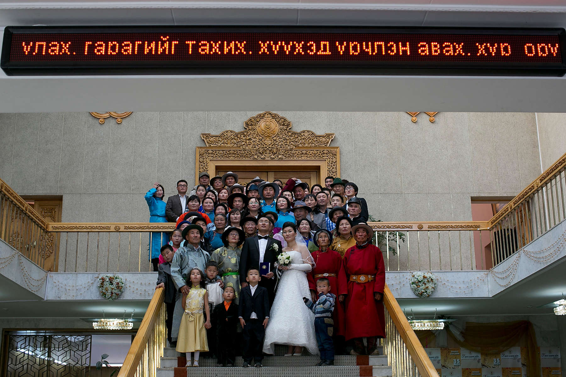 ULAANBATAAR, MONGOLIA - OCTOBER 18: A Mongolian wedding party poses for a photo at the wedding hall where many couples turned out to get married on a special day on the Lunar calendar weddings October 18, 2012 Ulaanbataar, Mongolia. Some 100 years ago, Mongolia gained independence from Qing China, and more than 20 years ago it removed itself from the Soviet Bloc. Since then, the country has been undergoing massive social, economic and political changes. The Oyu Tolgoi, the copper and gold mine is Mongolia's biggest foreign investment project to date adding an estimated 35% value to the country's GDP. Mongolia is a land of amazing contrasts and is the most sparsely populated country on earth with fewer than 3 million people. (Photo by Paula Bronstein/Getty Images)