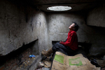 ULAAN BAATAR, MONGOLIA-MARCH 13 : Erdenetsetseg,36,  sits on a water pipe inside the sewer filled with garbage where she lives  March13, 2010  in Ulaan Baatar, Mongolia. Erdenetsetseg moved to the capitol city from a province five years ago, without work she collects cans and bottles to make enough money to buy a little food and her daily fix of vodka. Since 70 years of communist rule ended in 1990, Mongolia has become one of the most pro-business countries. While economic reforms have brought prosperity to Ulaan Baatar, there still widespread unemployment, some used to work in the now defunct state industries. Approximately over 35% of Mongolians live below the poverty line, many unable to buy basic food needed to survive. Social problems include depression, alcohol abuse, domestic violence and crime. Mongolia suffers with a very high number of alcoholics, all consuming cheap Mongolian vodka that is readily available to the poor and the unemployed, Many Mongolians have immigrated to the capitol city from the far away provinces seeking employment.  For the homeless during the winter this means extreme hardship, for some homeless living in the sewers means warmth verses dealing with temperatures dropping as low as -25C mid- Winter. This year Mongolia has experienced the worst winter in 30 years. (Photo by Paula Bronstein /Getty Images)