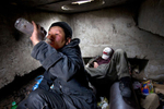 ULAAN BAATAR, MONGOLIA-MARCH 13 : Erdenetsetseg,36, drink vodka, living in a sewer filled with garbage  March 13 2010  in Ulaan Baatar, Mongolia. Erdenetsetseg moved to the capitol city from a province five years ago, without work she collects cans and bottles to make enough money to buy a little food and her daily fix of vodka.  Since 70 years of communist rule ended in 1990, Mongolia has become one of the most pro-business countries. While economic reforms have brought prosperity to Ulaan Baatar, there still widespread unemployment, some used to work in the now defunct state industries. Approximately over 35% of Mongolians live below the poverty line, many unable to buy basic food needed to survive. Social problems include depression, alcohol abuse, domestic violence and crime. Mongolia suffers with a very high number of alcoholics, all consuming cheap Mongolian vodka that is readily available to the poor and the unemployed, Many Mongolians have immigrated to the capitol city from the far away provinces seeking employment.  For the homeless during the winter this means extreme hardship, for some homeless living in the sewers means warmth verses dealing with temperatures dropping as low as -25C mid- Winter. This year Mongolia has experienced the worst winter in 30 years. (Photo by Paula Bronstein /Getty Images)