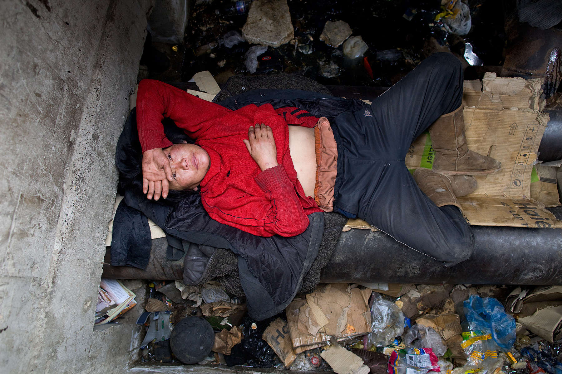 ULAAN BAATAR, MONGOLIA-MARCH 13 : Erdenetsetseg,36, rests on a water pipe, used as her bed living in a sewer filled with garbage  March 13 2010  in Ulaan Baatar, Mongolia. Erdenetsetseg moved to the capitol city from a province five years ago, without work she collects cans and bottles to make enough money to buy a little food and her daily fix of vodka.  Since 70 years of communist rule ended in 1990, Mongolia has become one of the most pro-business countries. While economic reforms have brought prosperity to Ulaan Baatar, there still widespread unemployment, some used to work in the now defunct state industries. Approximately over 35% of Mongolians live below the poverty line, many unable to buy basic food needed to survive. Social problems include depression, alcohol abuse, domestic violence and crime. Mongolia suffers with a very high number of alcoholics, all consuming cheap Mongolian vodka that is readily available to the poor and the unemployed, Many Mongolians have immigrated to the capitol city from the far away provinces seeking employment.  For the homeless during the winter this means extreme hardship, for some homeless living in the sewers means warmth verses dealing with temperatures dropping as low as -25C mid- Winter. This year Mongolia has experienced the worst winter in 30 years. (Photo by Paula Bronstein /Getty Images)