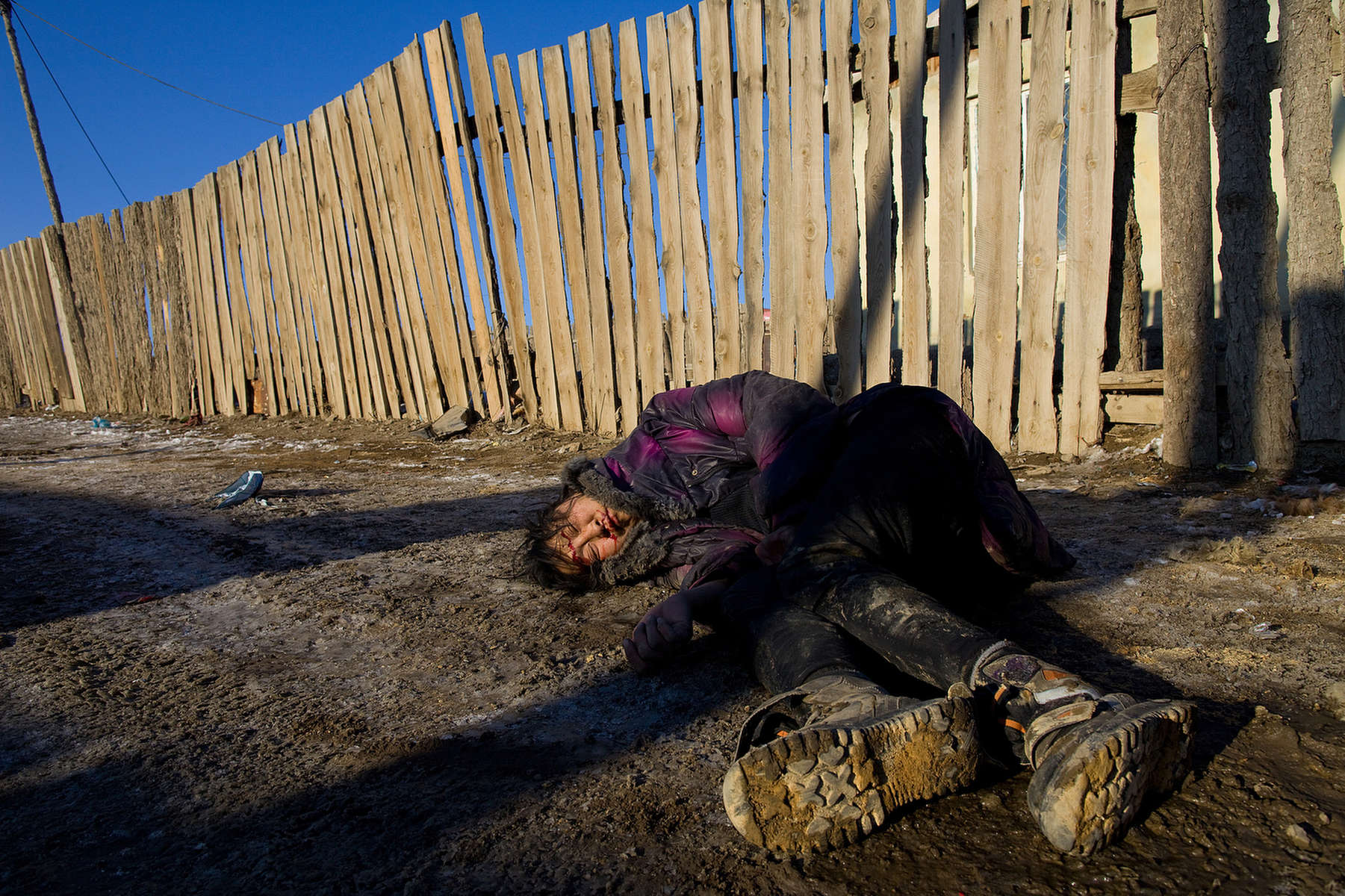A drunk woman, who fell and hit her head is left without any help,  passed out along the street  March 16, 2010  in Ulaan Baatar, Mongolia. Mongolia suffers with a very high number of alcoholics, all consuming cheap Mongolian vodka that is readily available to the poor and the unemployed, The problem is severe causing the number of street children to rise,  fleeing their abusive, dysfunctional homes. During the winter this means extreme hardship, for the homeless with temperatures dropping as low as -25C mid- Winter. This year Mongolia has experienced  extreme cold and snow during the worst winter in 30 years. Presently the government has declared an emergency requiring foreign aid to alleviate the impact of the {quote} Zud{quote} ( Mongolian term for a multiple natural disaster) caused by bitter cold and thick snow. Currently 1.5 mgoats, 921,000 sheep, 169,000 cows and yaks, 89,000 horses and 1,500 camels had died according to the various UN agency reports. Many Mongolians have immigrated to the capitol city from the far away provinces seeking employment, living in rented traditional circular felt yurts with no running water or electricity.(Photo by Paula Bronstein /Getty Images)