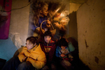 ULAAN BAATAR, MONGOLIA-MARCH 16 :  Otgonjargal, 10, (right) sister Zulaa,18, (center) and friend Sainaa (left) sit in a freezing cold house without electricity March 16, 2010  in Ulaan Baatar, Mongolia. They spend their time on the streets, not at school. They frequent the Save The Children drop - in center on weekdays and many times stay with other street children. Mongolia suffers with a very high number of alcoholics, all consuming cheap Mongolian vodka that is readily available to the poor and the unemployed, Many Mongolians have immigrated to the capitol city from the far away provinces seeking employment, living in rented traditional circular felt yurts with no running water or electricity. The problem is severe causing the number of street children to rise,  fleeing their abusive, dysfunctional homes. Some children are regularly beaten at home, and for the impoverished it is common to send the child out to make money. During the winter this means extreme hardship, the children out on the city streets are dealing with temperatures dropping as low as -25C mid- Winter. This year Mongolia has experienced the worst winter in 30 years. Presently the government has declared an emergency requiring foreign aid to alleviate the impact of the {quote} Zud{quote} ( Mongolian term for a multiple natural disaster) caused by bitter cold and thick snow that has effected 68% of the provinces. (Photo by Paula Bronstein /Getty Images)