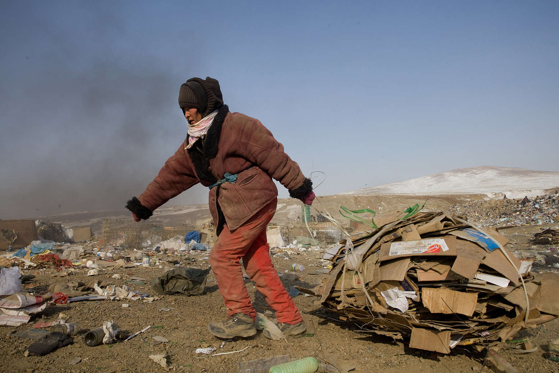 ULAAN BAATAR, MONGOLIA-MARCH 5 :  A Mongolian woman drags cardboard to the truck working collecting and recycling the garbage at a dump March 5, 2010  in Ulaan Baatar, Mongolia. Working at the garbage dump means extreme hardship, long hours outside in frigid temperatures dropping below -25C in the Winter as Mongolia experienced one of the worst Winter in 30 years. Presently the government has declared an emergency requiring foreign aid to alleviate the impact of the {quote} Zud{quote} ( Mongolian term for a multiple natural disaster) caused by bitter cold and thick snow. Currently 1.5 million goats,  921,000 sheep, 169,000 cows and yaks, 89,000 horses and 1,500 camels had died according to the various UN agency reports. Many Mongolians have immigrated to the capitol city from the far away provinces seeking employment, living in rented traditional circular felt yurts with no running water or electricity.(Photo by Paula Bronstein /Getty Images)
