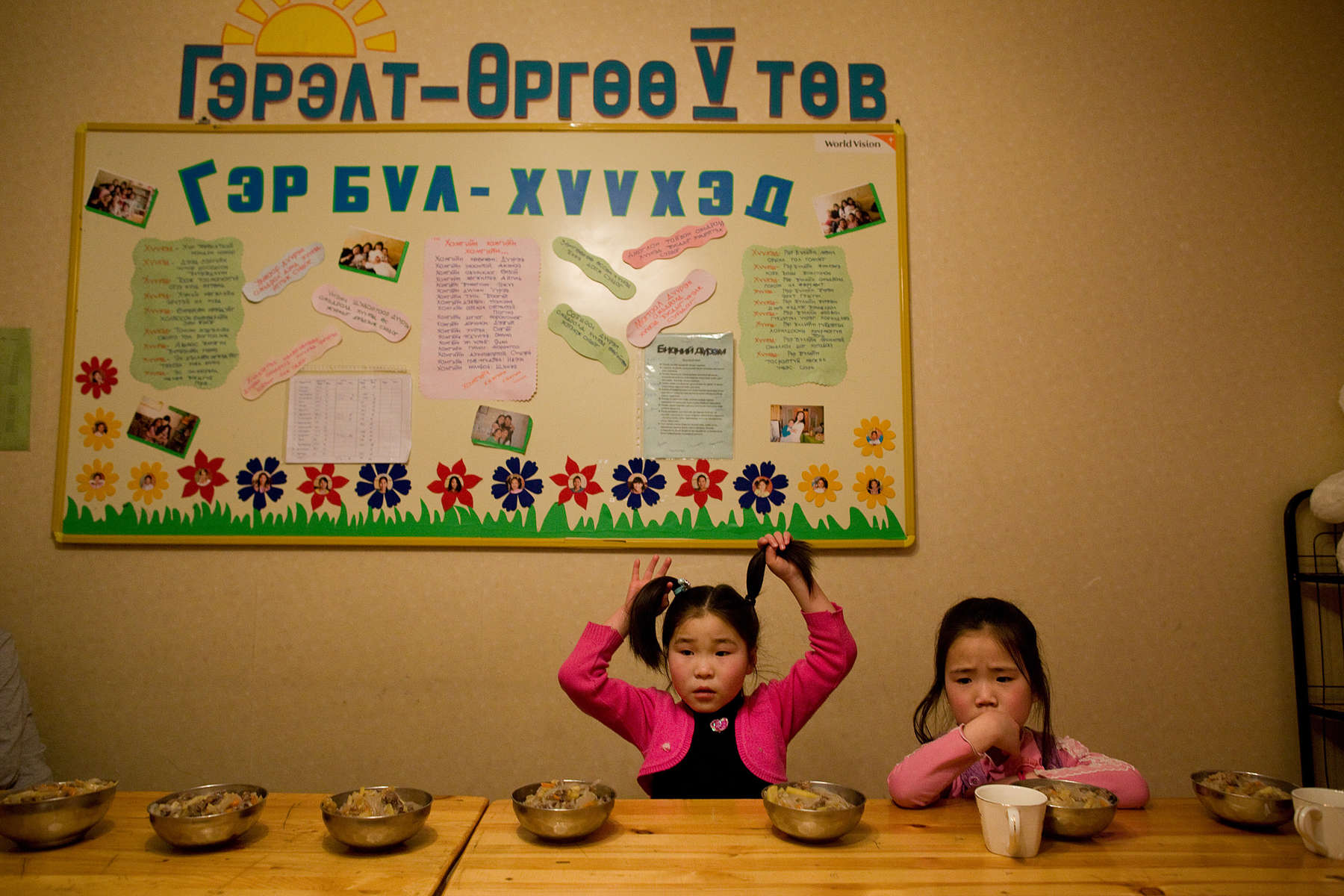 ULAAN BAATAR, MONGOLIA-MARCH 10 :  At the Lighthouse girls shelter girls wait for everyone to sit down for dinner March 10, 2010  in Ulaan Baatar, Mongolia. The Lighthouse is a World Vision sponsored shelter where 18 girls live from age 5-18. After that the state labels them as being abandoned or orphaned they go from the temporary welfare center to the more permanent shelters like the Lighthouse wher ethey live together is a home, sleeping, eating and going to public schools. Mongolia suffers with a very high number of alcoholics, all consuming cheap Mongolian vodka that is readily available to the poor and the unemployed, Many Mongolians have immigrated to the capitol city from the far away provinces seeking employment, living in rented traditional circular felt yurts with no running water or electricity. The problem is severe causing the number of street children to rise,  fleeing their abusive, dysfunctional homes. Some children are regularly beaten at home, and for the impoverished it is common to send the child out to make money. During the winter this means extreme hardship, the children out on the city streets are dealing with temperatures dropping as low as -25C mid- Winter. This year Mongolia has experienced the worst winter in 30 years. Presently the government has declared an emergency requiring foreign aid to alleviate the impact of the {quote} Zud{quote} ( Mongolian term for a multiple natural disaster) caused by bitter cold and thick snow that has effected 68% of the provinces. (Photo by Paula Bronstein /Getty Images)