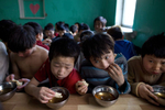 ULAAN BAATAR, MONGOLIA-MARCH 11 :  Mongolian street kids eat a midday snack of tea and bread at the child detention center March 11, 2010  in Ulaan Baatar, Mongolia. The police picked up a dozen boys to get them off the streets in the cold weather housing them at the Ulaan Bataar Child Welfare/ detention center sponsored by World Vision. There about 45 kids live in the dormitory where they get hot food, showers, and some educational activities until their parents claim them. Before the children can go into more permanent shelters they are kept in the welfare center for up to 6 months. After that the state labels them as being abandoned or orphaned. Mongolia suffers with a very high number of alcoholics, all consuming cheap Mongolian vodka that is readily available to the poor and the unemployed, Many Mongolians have immigrated to the capitol city from the far away provinces seeking employment, living in rented traditional circular felt yurts with no running water or electricity. The problem is severe causing the number of street children to rise,  fleeing their abusive, dysfunctional homes. Some children are regularly beaten at home, and for the impoverished it is common to send the child out to make money. During the winter this means extreme hardship, the children out on the city streets are dealing with temperatures dropping as low as -25C mid- Winter. This year Mongolia has experienced the worst winter in 30 years. Presently the government has declared an emergency requiring foreign aid to alleviate the impact of the {quote} Zud{quote} ( Mongolian term for a multiple natural disaster) caused by bitter cold and thick snow that has effected 68% of the provinces. (Photo by Paula Bronstein /Getty Images)
