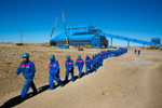 KHANBOGD-SOUTH GOBI DESERT, MONGOLIA - OCTOBER 11:  Chinese construction workers  march together as they leave on a lunch break at the Oyu Tolgoi mine October 11, 2012 located in the south Gobi desert, Khanbogd region, Mongolia. About 2,500  Chinese workers are contracted to help with construction onsite. The Oyu Tolgoi copper and gold mine (translated means Turquiose Hill) is a combined open pit and underground mining project.  While the construction continues open pit mining is currently underway with full production expected later in 2012. When the mine starts full operation the country will be set to become one of the world's top copper and gold producers with estimates of 450,000 tons of copper and 330,000 ounces of gold. Financing for the project has come in part from the Rio Tinto Group and an investment agreement between Ivanhoe Mines and the government of Mongolia. Mongolia's largest foreign investment project to date is projected to increase the country's GDP by 35%. Many estimate Mongolia to be the world's fastest growing economy with an estimated $1.3 trillion in untapped mineral resources. (Photo by Paula Bronstein/Getty Images)