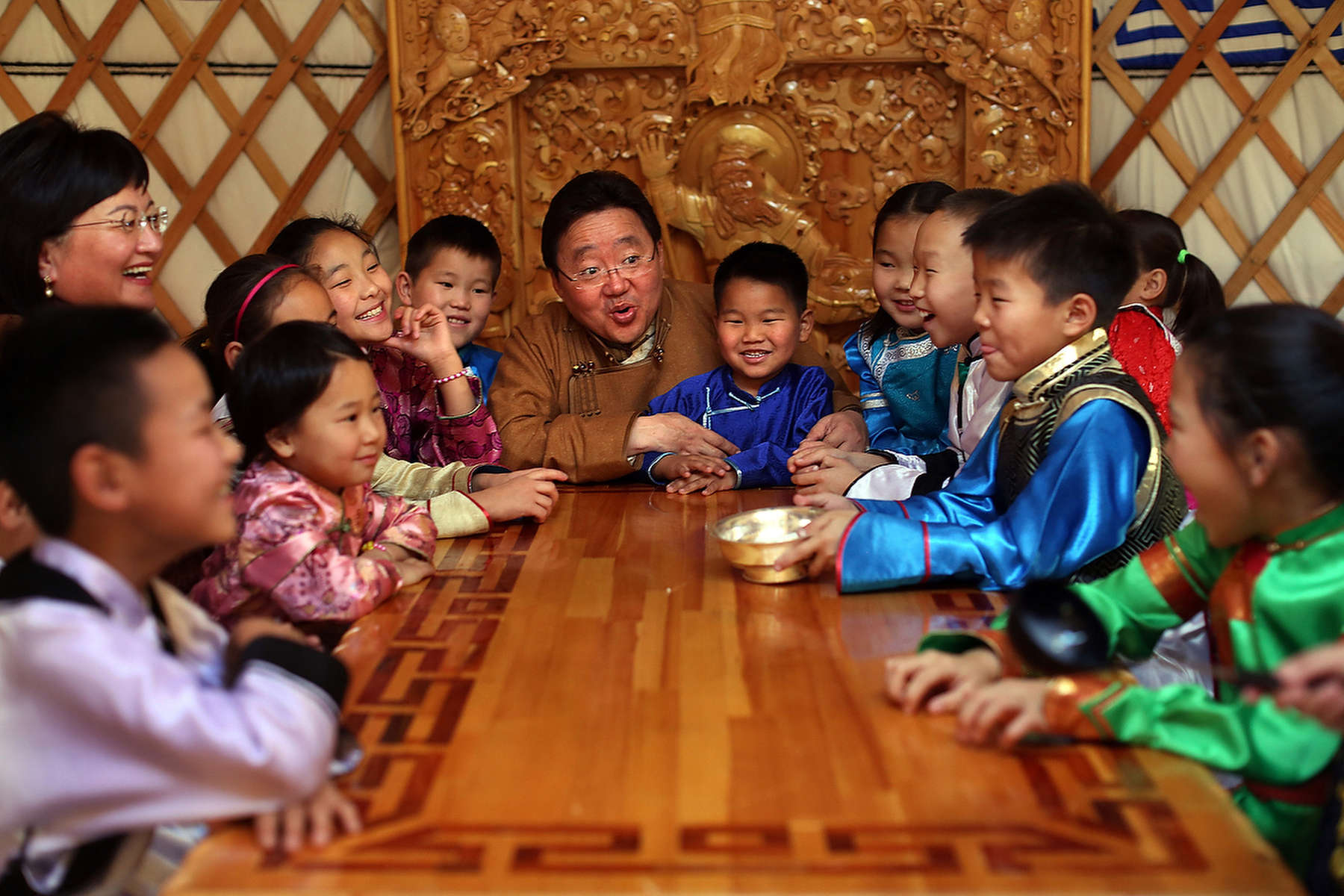 ULAANBATAAR, MONGOLIA - OCTOBER 26: President Tsakhiagiin Elbegdorj and first lady, Bolormaa Khajidsuren (L) share laughs with their foster children while drinking milk tea inside a Ger at the presidential residence October 26, 2012 in Ulaanbataar, Mongolia. President Tsakhiagiin Elbegdorj was elected  on May 25, 2009, he had previously served two terms as Prime Minister and held the positions of Deputy Speaker and Majority Leader in Parliament. The first lady, Bolormaa Khajidsuren is a mother of 4 children, and the extended Presidential family includes 20 foster children coming from a variety of government children's homes. Some 100 years ago, Mongolia gained independence from Qing China, and more than 20 years ago it removed itself from the Soviet Bloc. Since then, the country has been undergoing massive social, economic and political changes. The Oyu Tolgoi copper and gold mine is Mongolia's biggest foreign investment project to date adding an estimated 35% value to the country's GDP. Mongolia is a land of amazing contrasts and is the most sparsely populated country on earth with fewer than 3 million people. (Photo by Paula Bronstein/Getty Images)