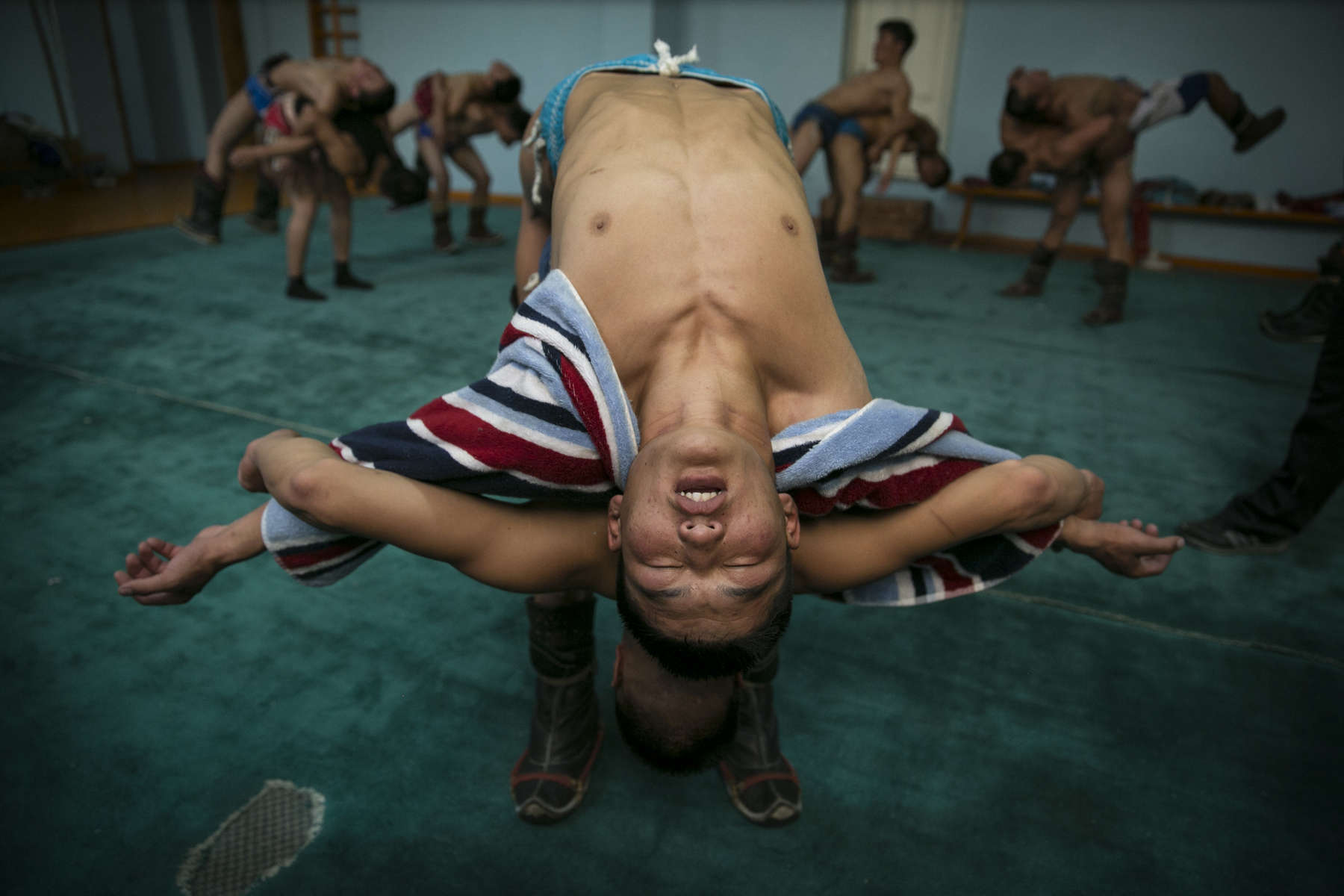 Mongolian wrestlers go through warm up exercises at a local wrestling school in Ulan Batar. Mongolia is the most sparsely populated country on earth, but its people are some of the strongest. In Mongolia, wrestling is the most important sport that runs deep into its culture along with horsemanship and archery. Going back for hundreds of years, history books tell the story of how Genghis Khan considered wrestling to be an important way to keep his army combat ready while back in the Qing Dynasty (1646–1911) regular wrestling events were held. In Mongolia's capitol city, Ulan Batar is home to many wrestling schools where almost daily you can see dozens of young men sweating in crowded gyms while in schools both girls and boys are taught some wrestling techniques.While my photo story gives a real behind the scenes look, it is unusual for a woman to document this macho scene of sweat and endurance.