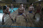 Mongolian wrestlers practice their squats trying to strengthen their thighs during practice at a local wrestling school. Mongolia is the most sparsely populated country on earth, but its people are some of the strongest. In Mongolia, wrestling is the most important sport that runs deep into its culture along with horsemanship and archery. Going back for hundreds of years, history books tell the story of how Genghis Khan considered wrestling to be an important way to keep his army combat ready while back in the Qing Dynasty (1646–1911) regular wrestling events were held. In Mongolia's capitol city, Ulan Batar is home to many wrestling schools where almost daily you can see dozens of young men sweating in crowded gyms while in schools both girls and boys are taught some wrestling techniques.While my photo story gives a real behind the scenes look, it is unusual for a woman to document this macho scene of sweat and endurance.