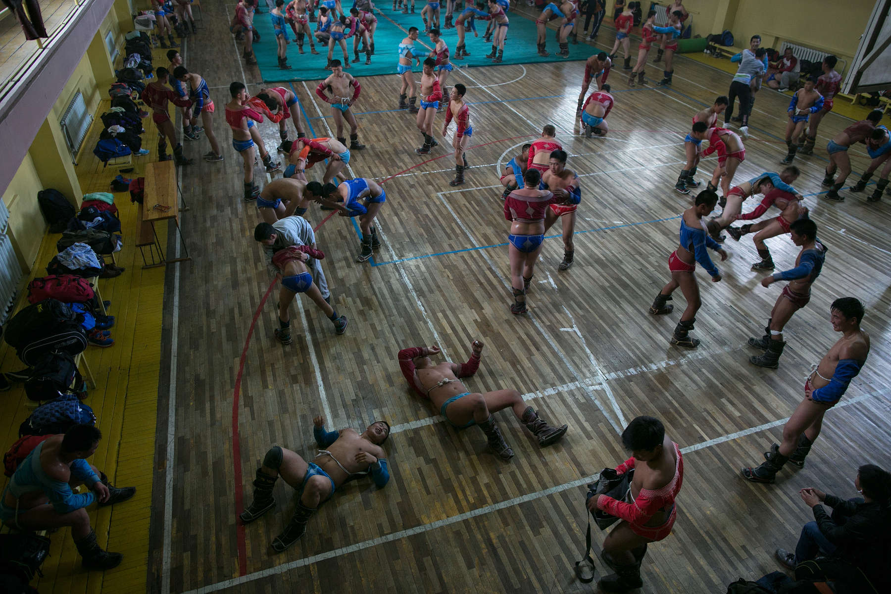 Hundreds of Mongolian wrestlers practice at a local wrestling school in Ulan Bataar. Mongolia is the most sparsely populated country on earth, but its people are some of the strongest. In Mongolia, wrestling is the most important sport that runs deep into its culture along with horsemanship and archery. Going back for hundreds of years, history books tell the story of how Genghis Khan considered wrestling to be an important way to keep his army combat ready while back in the Qing Dynasty (1646–1911) regular wrestling events were held. In Mongolia's capitol city, Ulan Batar is home to many wrestling schools where almost daily you can see dozens of young men sweating in crowded gyms while in schools both girls and boys are taught some wrestling techniques.While my photo story gives a real behind the scenes look, it is unusual for a woman to document this macho scene of sweat and endurance.