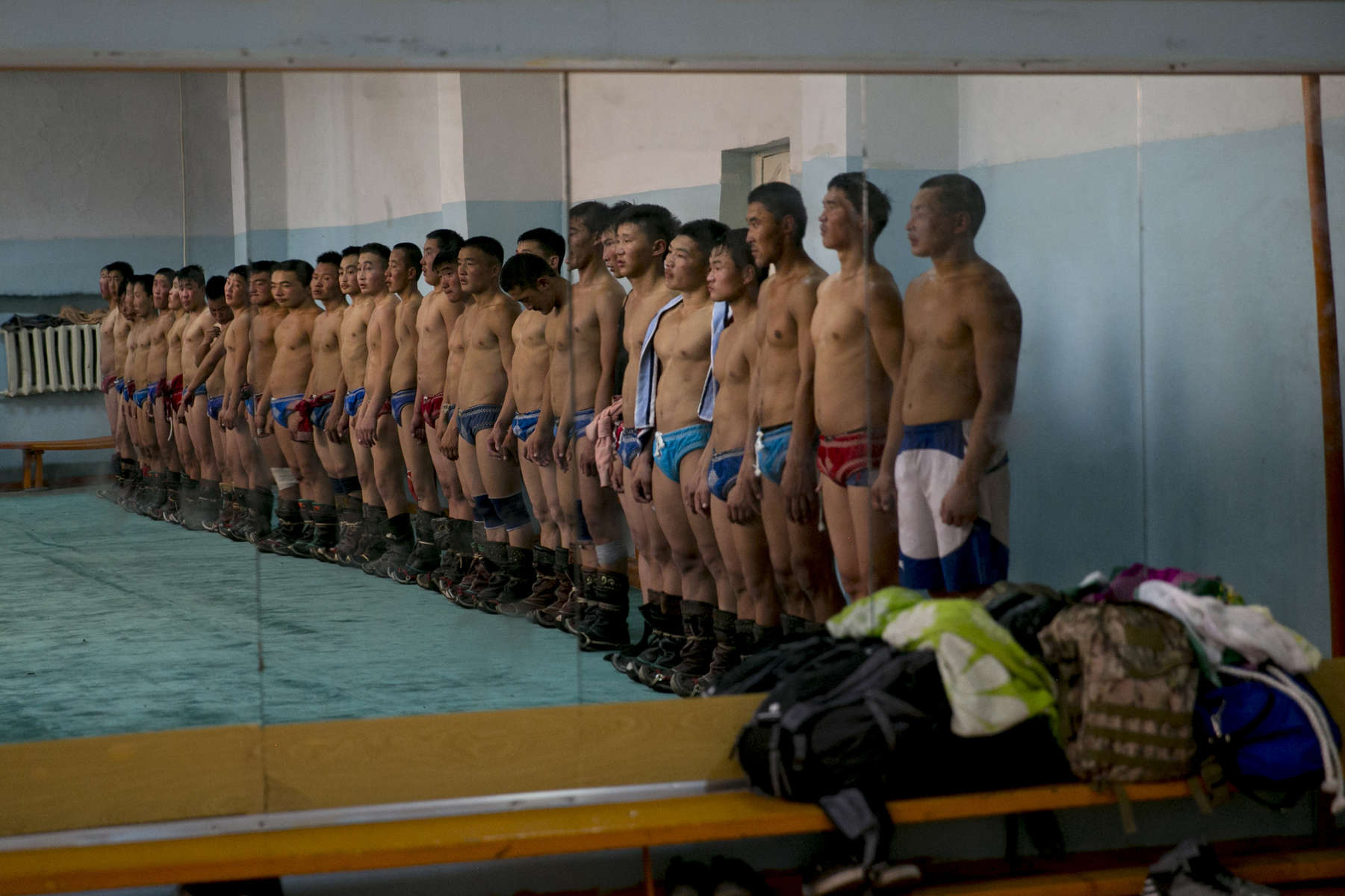 Mongolian wrestlers stand at attention before starting their practice at a local wrestling school. Mongolia is the most sparsely populated country on earth, but its people are some of the strongest. In Mongolia, wrestling is the most important sport that runs deep into its culture along with horsemanship and archery. Going back for hundreds of years, history books tell the story of how Genghis Khan considered wrestling to be an important way to keep his army combat ready while back in the Qing Dynasty (1646–1911) regular wrestling events were held. In Mongolia's capitol city, Ulan Batar is home to many wrestling schools where almost daily you can see dozens of young men sweating in crowded gyms while in schools both girls and boys are taught some wrestling techniques.While my photo story gives a real behind the scenes look, it is unusual for a woman to document this macho scene of sweat and endurance.