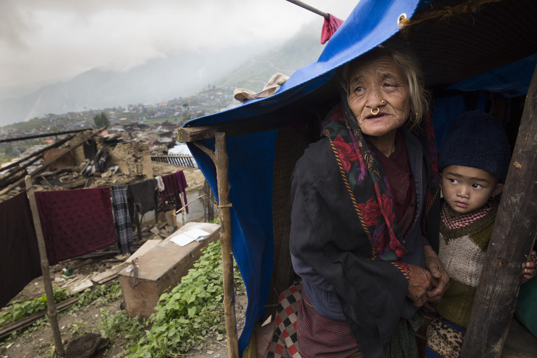 BARPAK, NEPAL -MAY 1, 2015:. Dhan Maya Ghale,68 holds her grandson, Sujal,3, hiding from the rain in a temporary shelter in Barpak where 60% of the village has been destroyed. The village is amongst the largest in Gorkha province with a population of around 10-12,000. Around 57-60 died. So far almost 6,000 people have died in Nepal\'s worst earthquake in 80 years.  (Photo by Paula Bronstein/ for the Wall Street Journal)