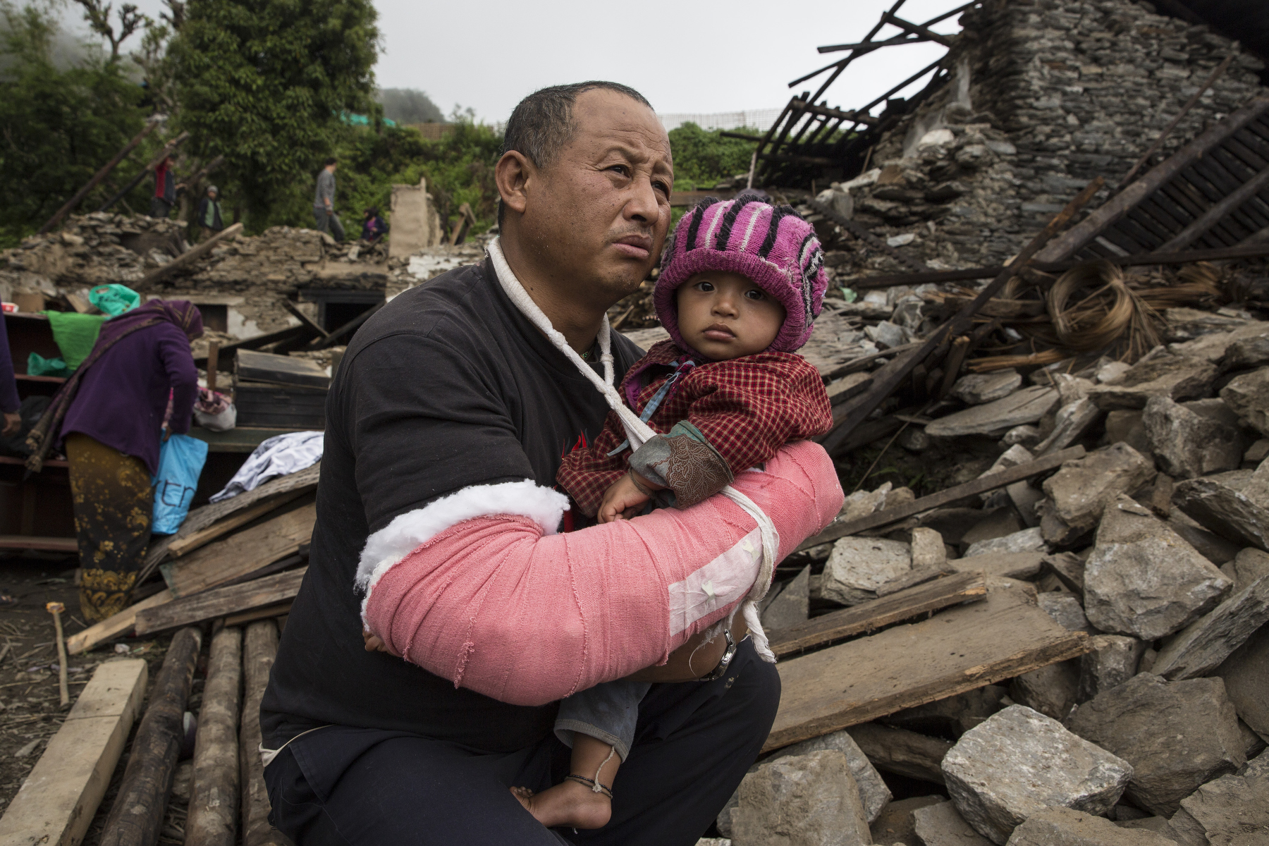 BARPAK, NEPAL -MAY 1, 2015:. Khem Ghale holds his son Milan,10 months who he rescued from his house as it collapsed. In Barpak where 60% of the village has been destroyed. The village is amongst the largest in Gorkha province with a population of around 10-12,000. Around 57-60 died. So far almost 6,000 people have died in Nepal\'s worst earthquake in 80 years.  (Photo by Paula Bronstein/ for the Wall Street Journal)