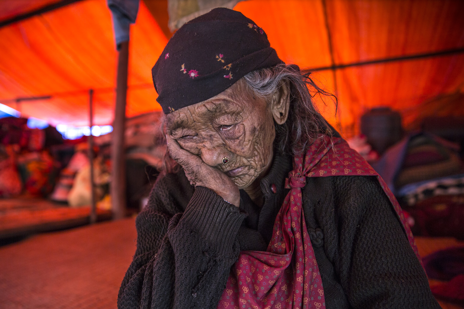 BARPAK, NEPAL -MAY 1, 2015:. 99 year old Kalimaya Gurung rests under a tarp as her family clears debris in their homes. She refuses to leave her village, she was born in Barpak and chooses to die there. In Barpak 60% of the village has been destroyed. The village is amongst the largest in Gorkha province with a population of around 10-12,000, 57-60 died. So far almost 6,000 people have died in Nepal\'s worst earthquake in 80 years.  (Photo by Paula Bronstein/ for the Wall Street Journal)
